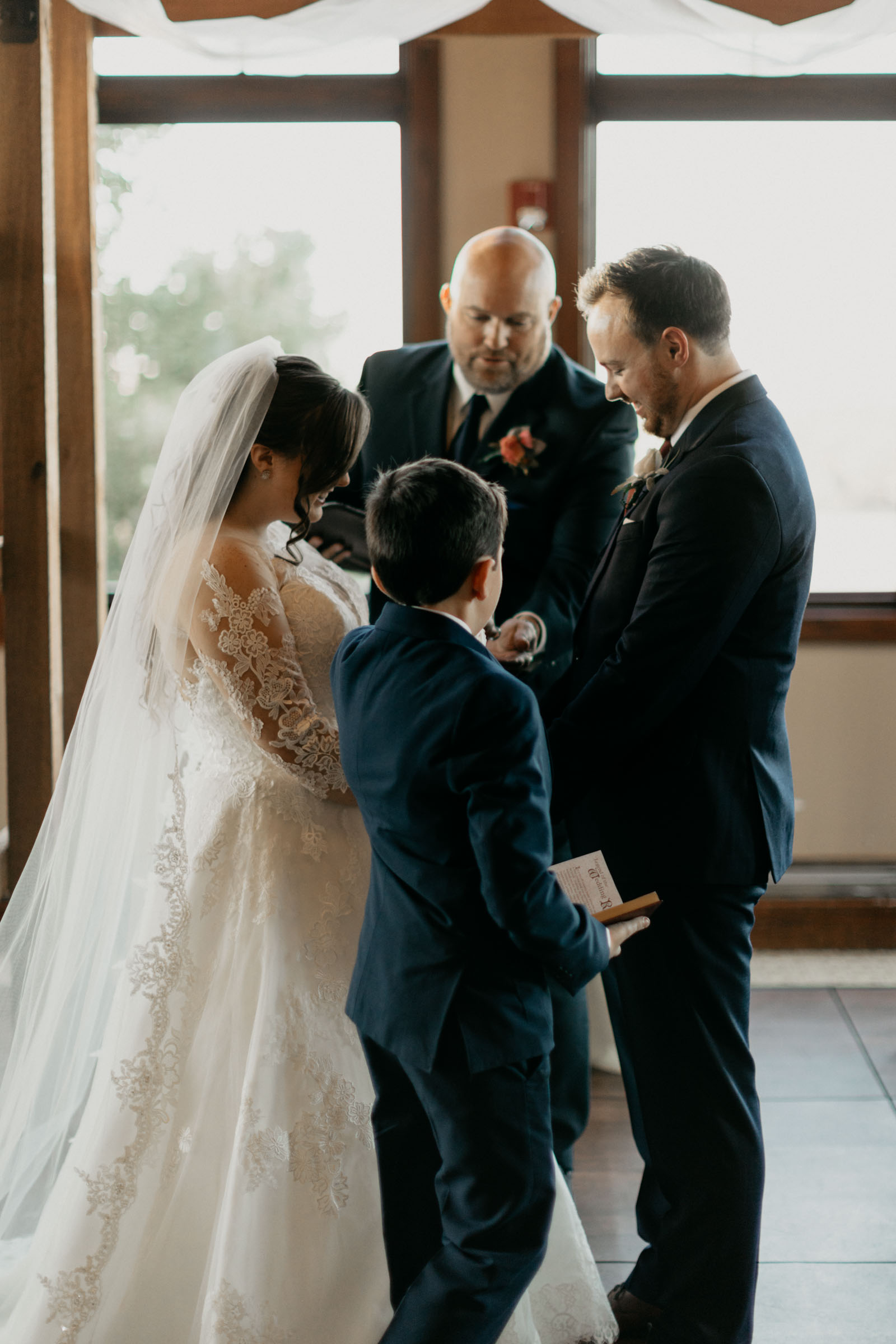 bride and groom holding hands and exchanging rings during their wedding ceremony