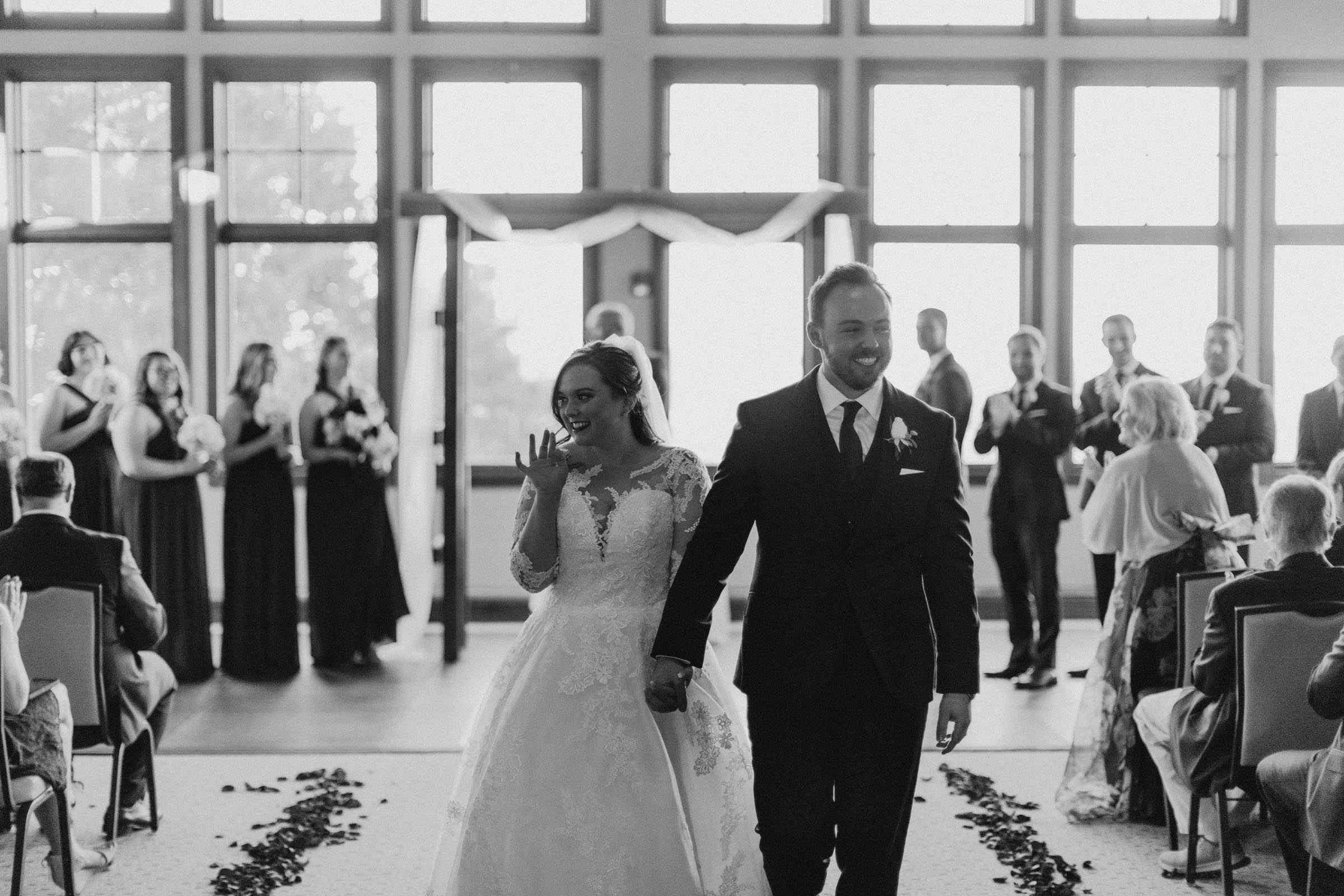 Black and white photo of married couple leaving their ceremony