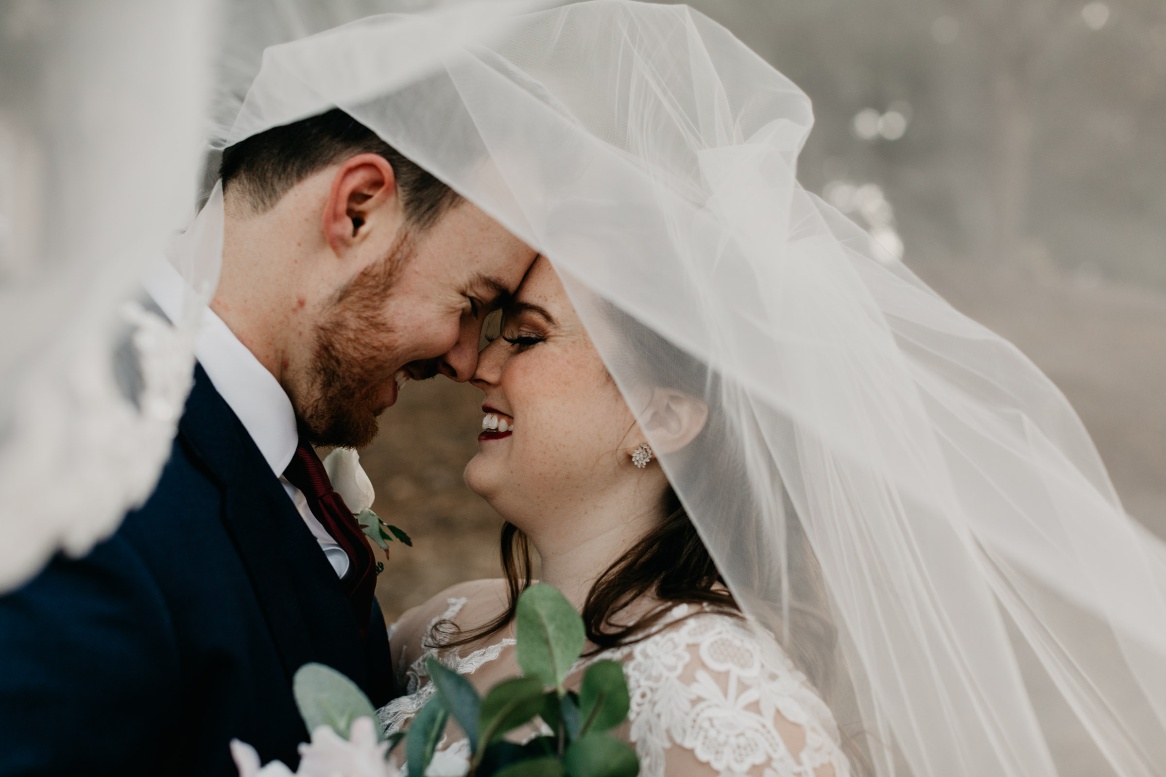 bride and groom under the brides veil on wedding day
