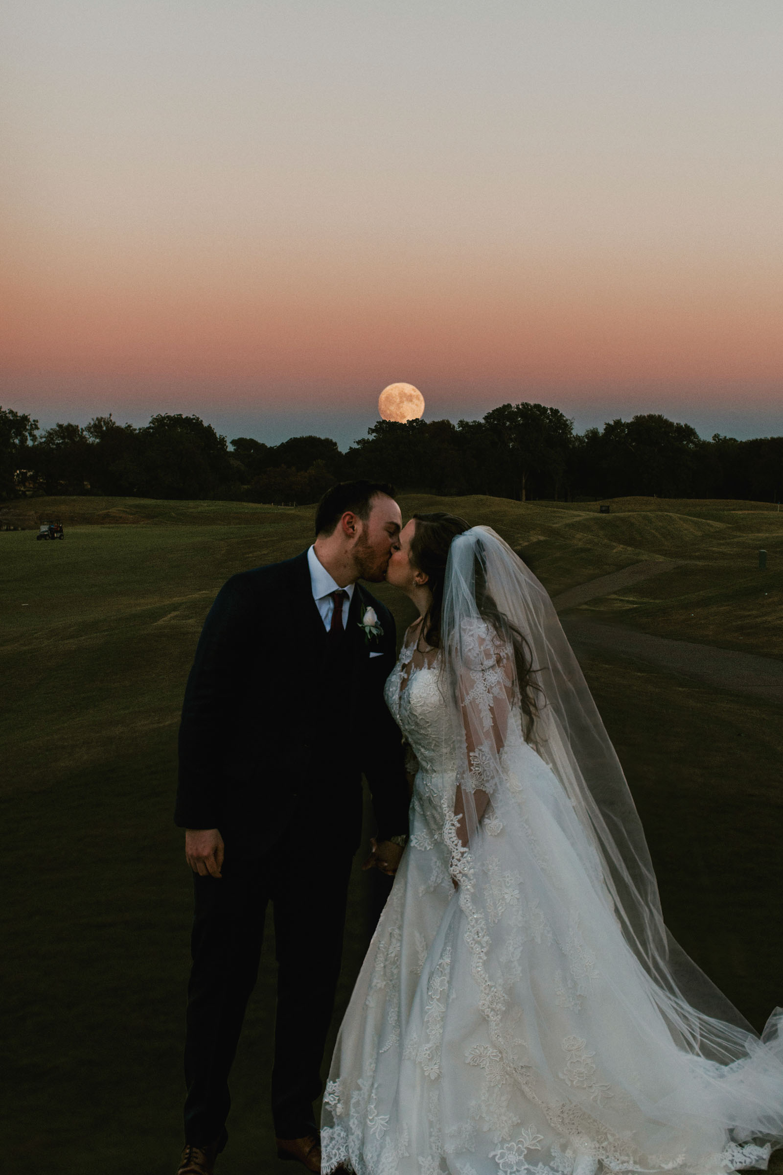 photo of bride and groom kissing as the moon rises