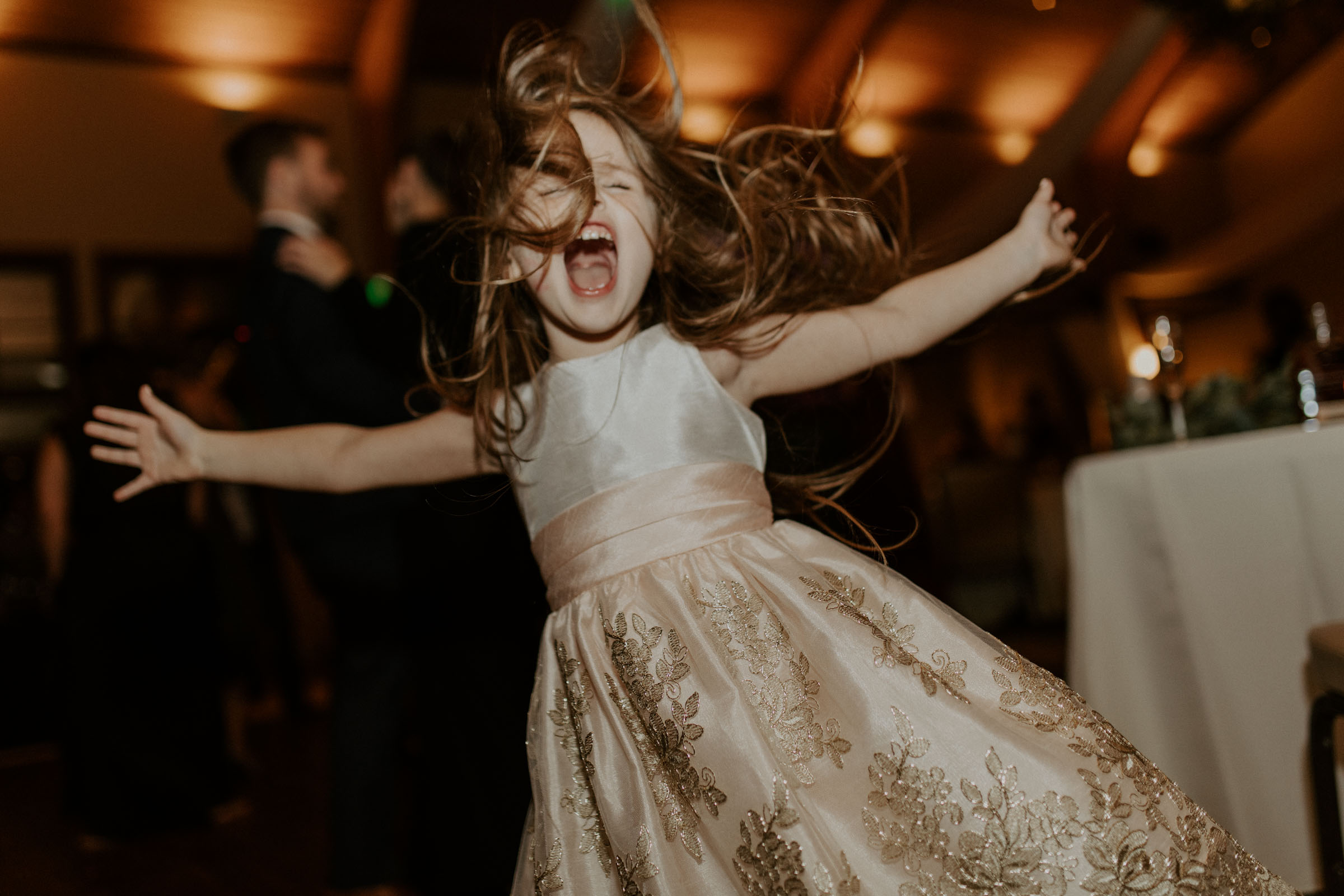 adorable flower girl jumping around at wedding reception