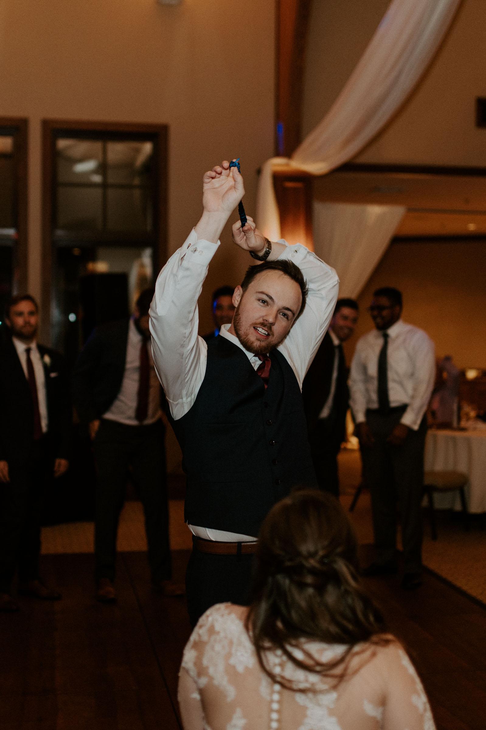 groom taking off garter during wedding reception
