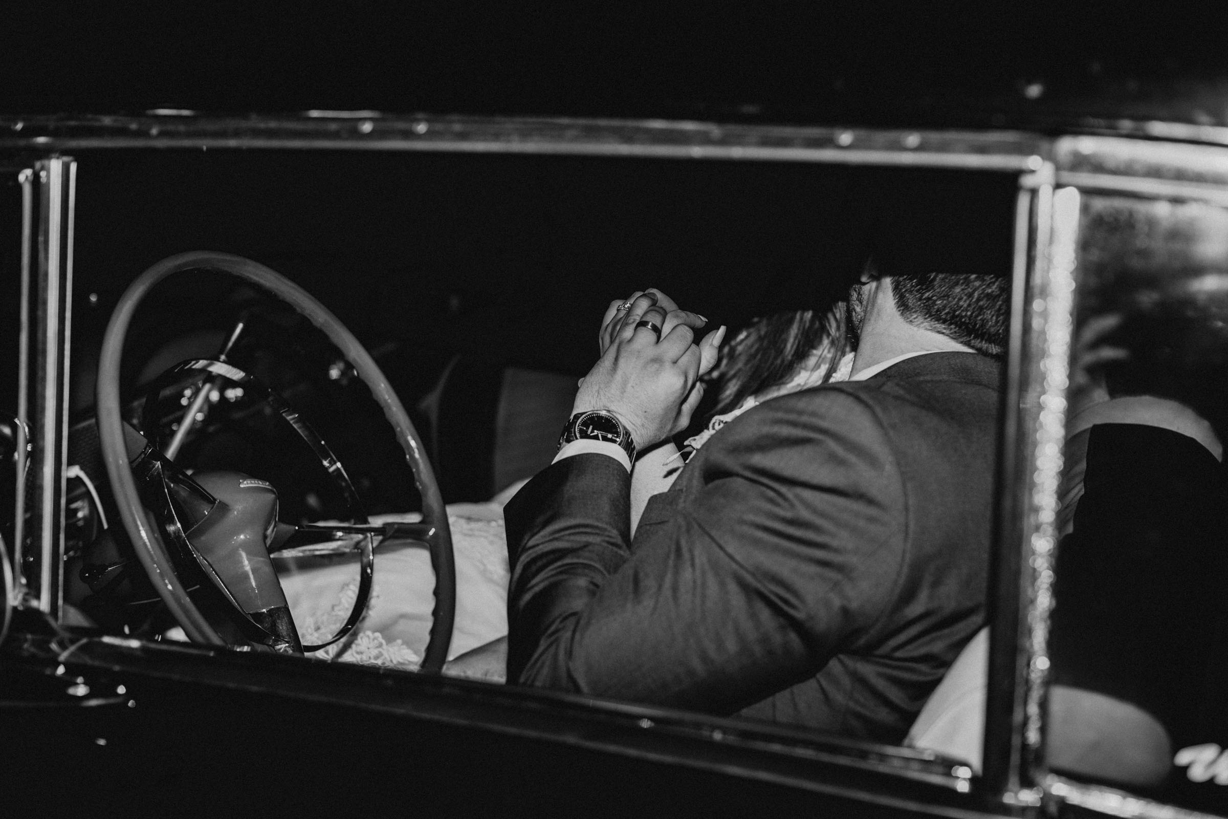 Bride and groom sitting in their vintage getaway car before they leave their reception