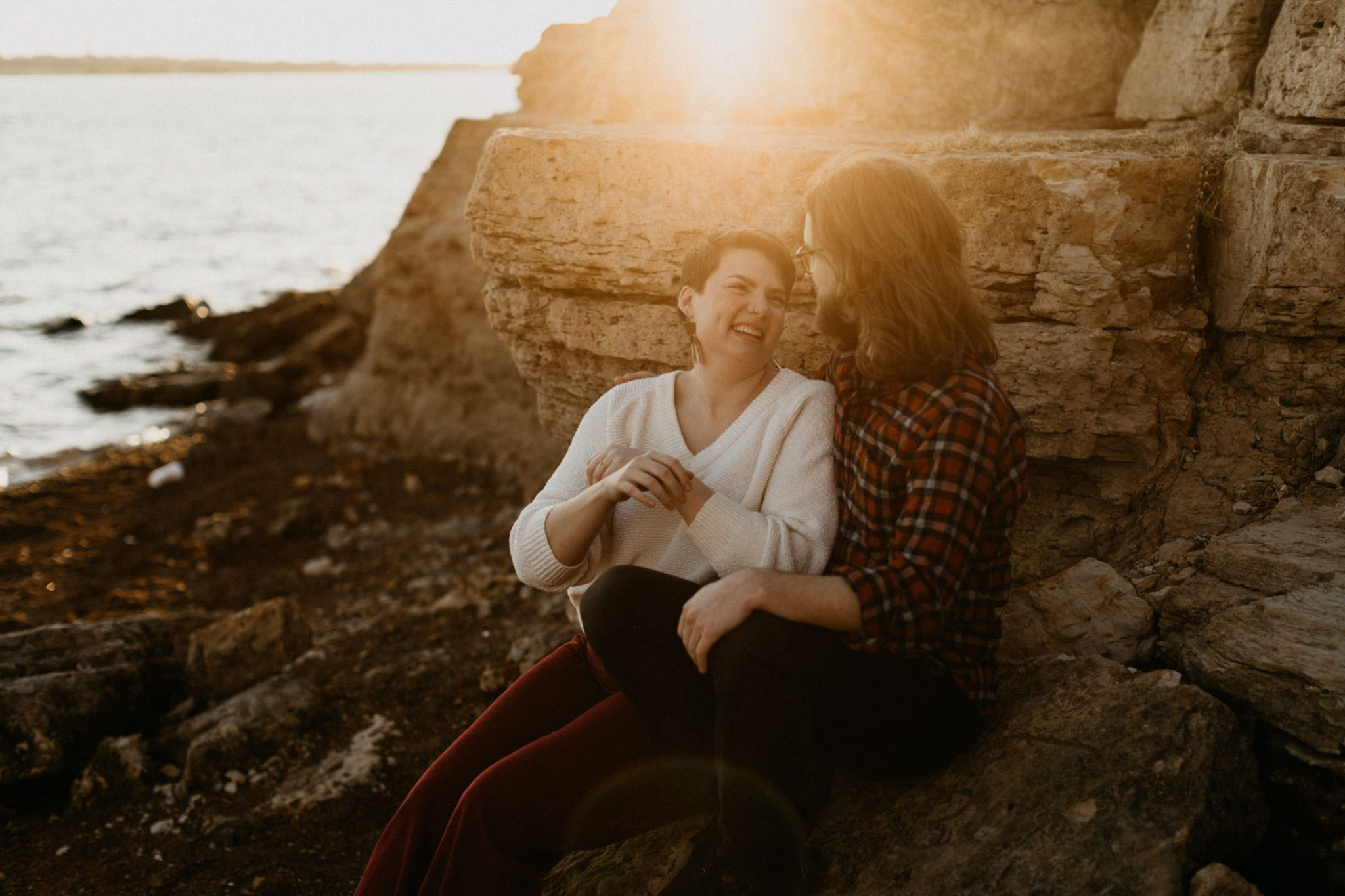 Cute couple sitting and cuddling outdoors for their engagement session