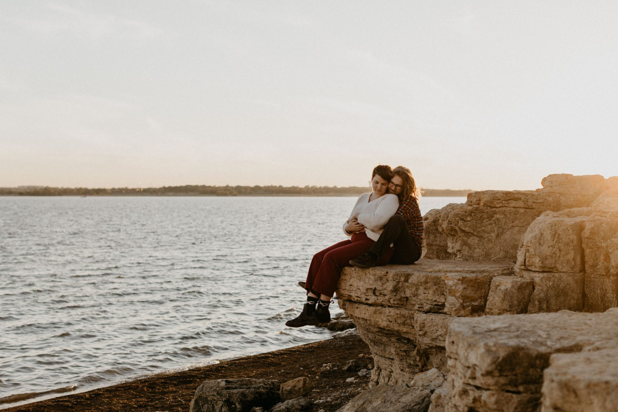Couple sitting on the edge of a rock during their engagement session