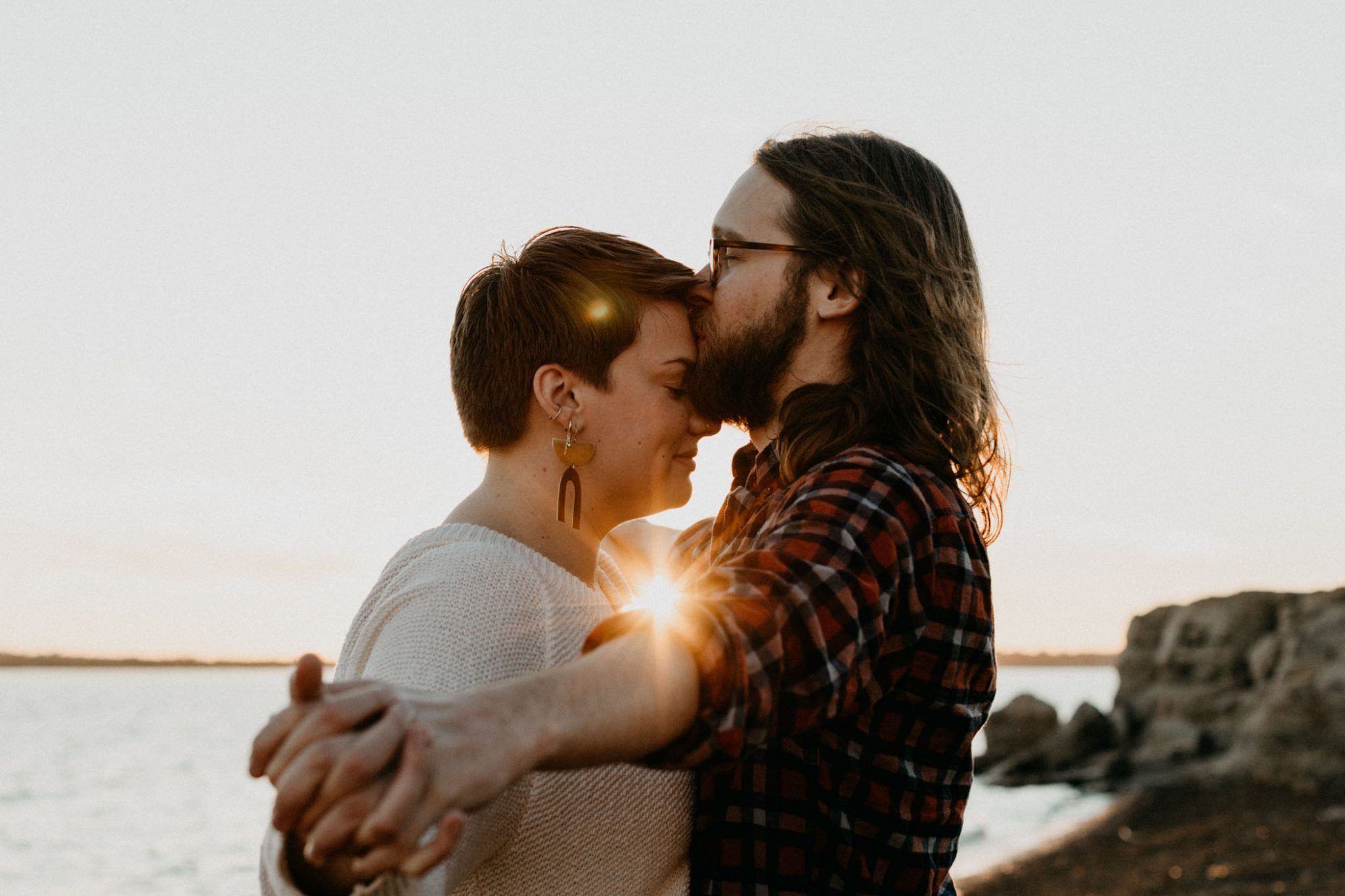 boy kissing girl at golden hour