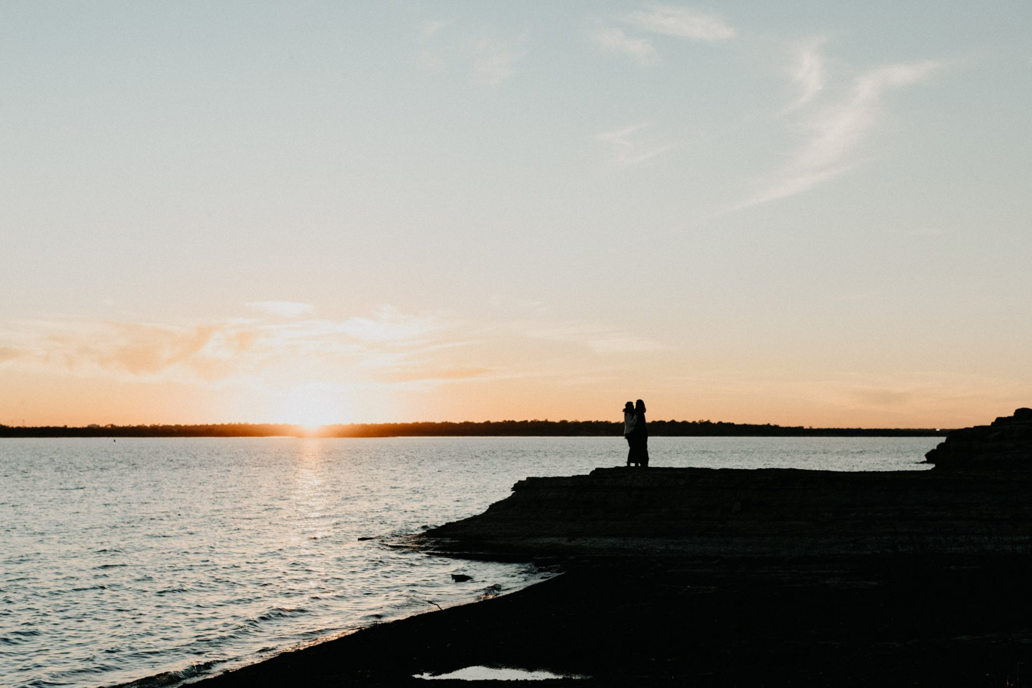 wide angle photograph of couple standing next to the water at sunset