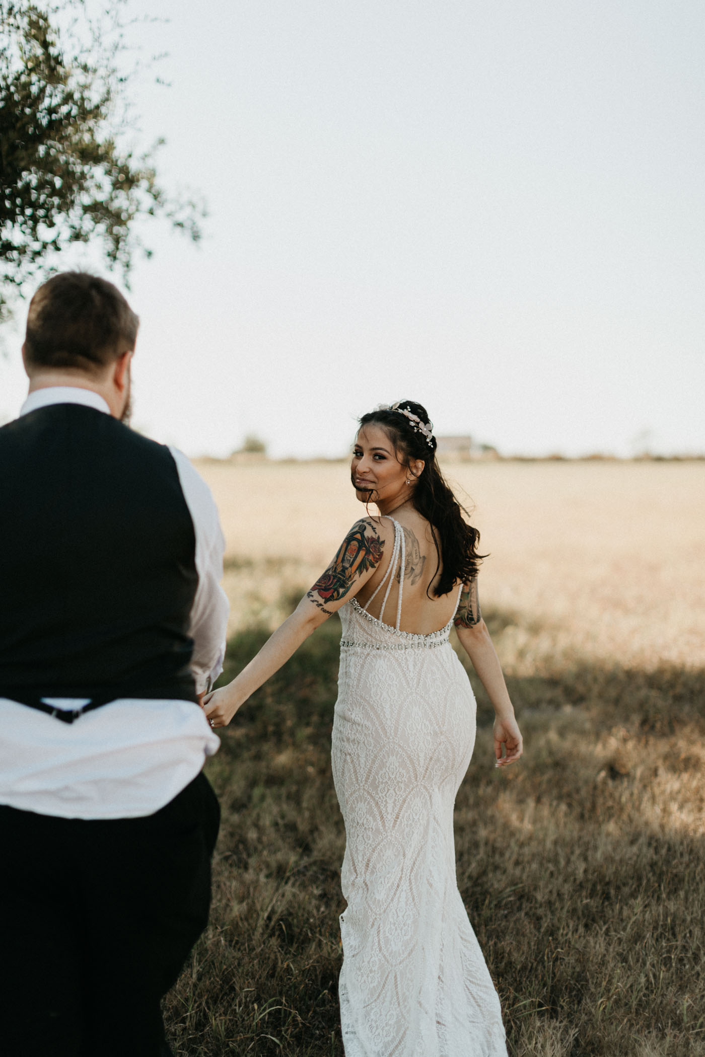 Bride and groom walking and holding hands in a field after wedding ceremony