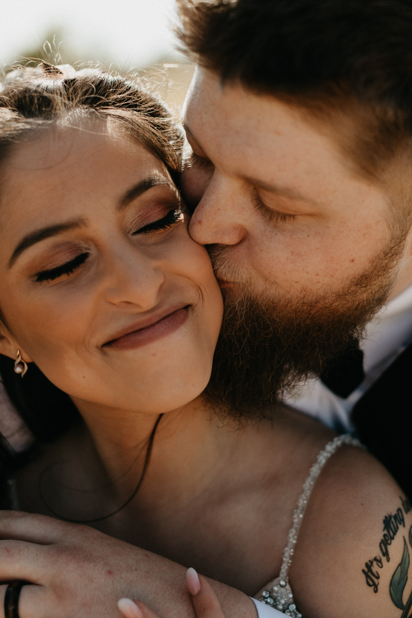 Close up photo of groom kissing bride on the cheek after their North Texas wedding ceremony