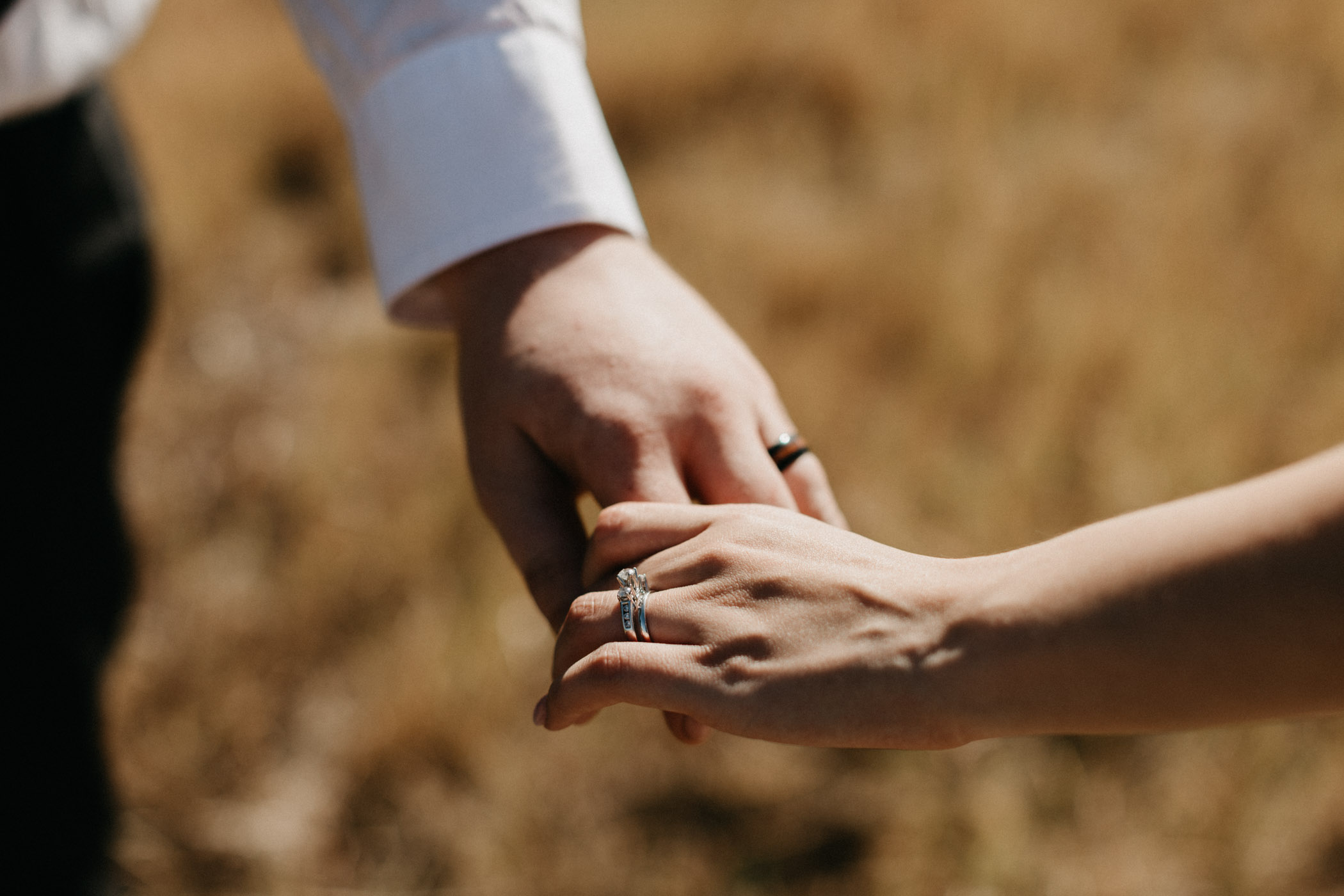 Bride and groom holding hands and walking in a field showing off their wedding rings