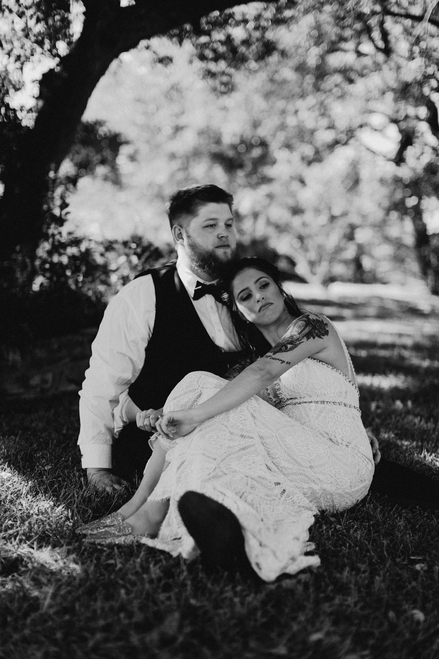 Bride and groom sitting in the grass under a tree for a romantic photo