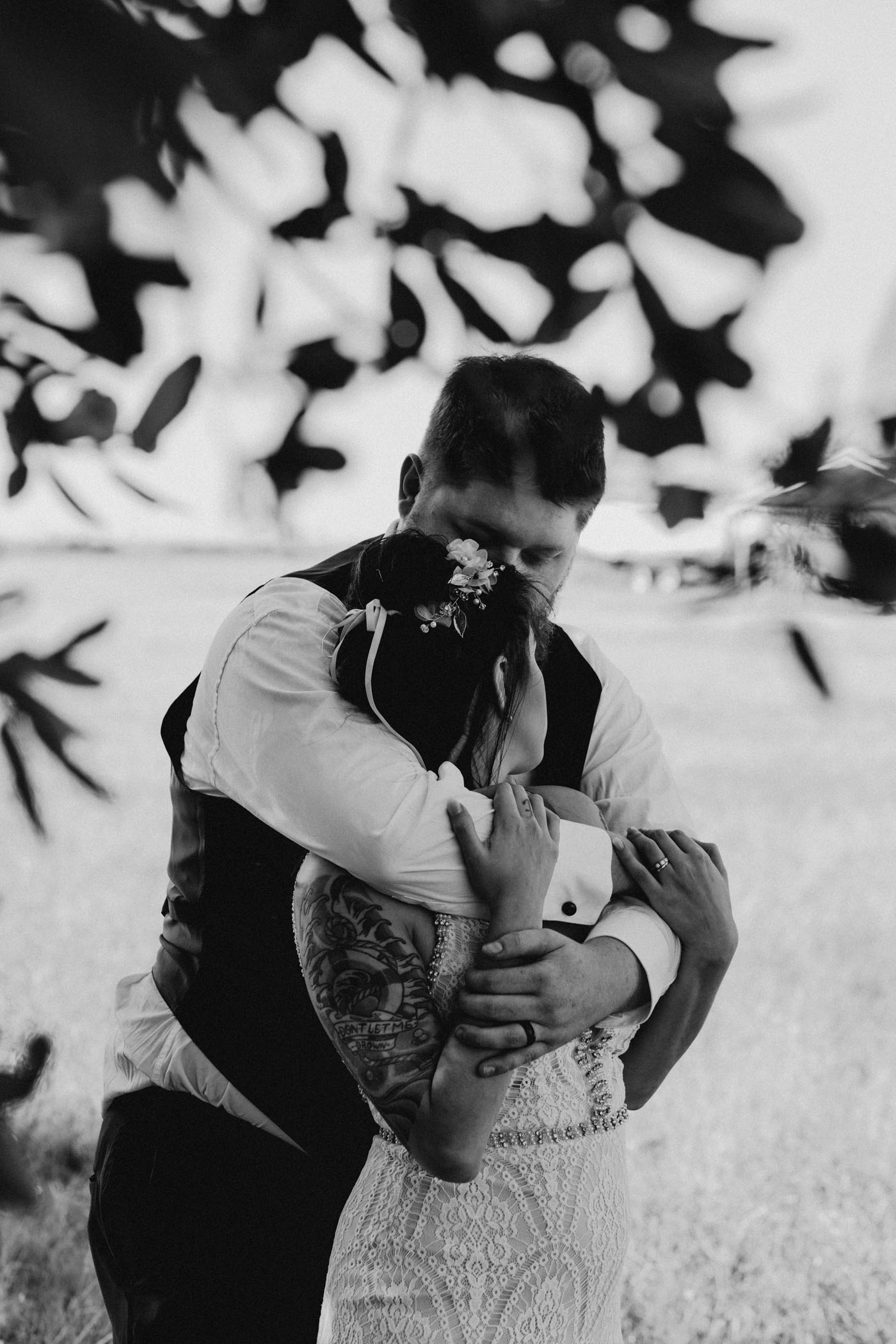 black and white of groom hugging bride from behind