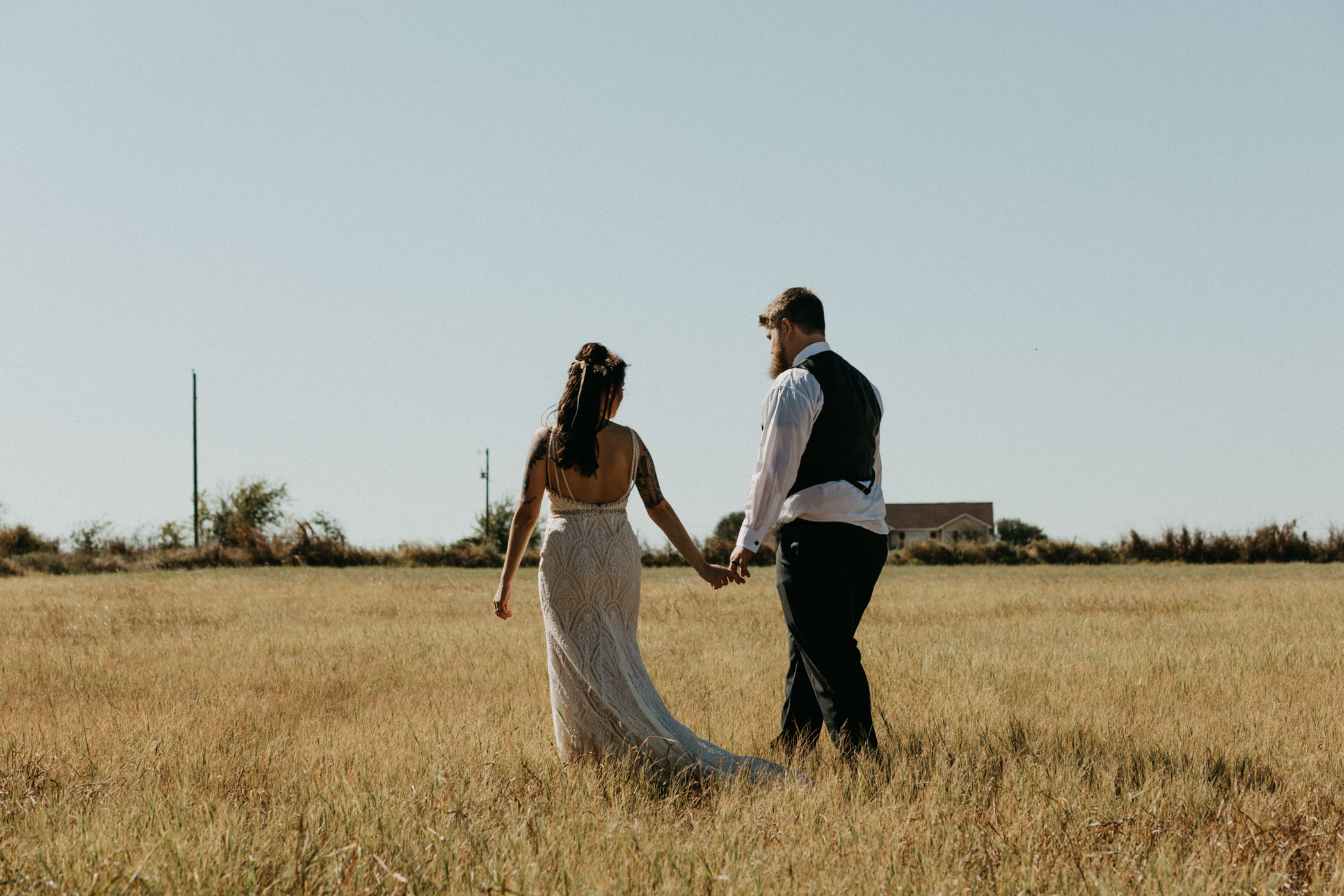 Bride and groom walking in a field after wedding ceremony