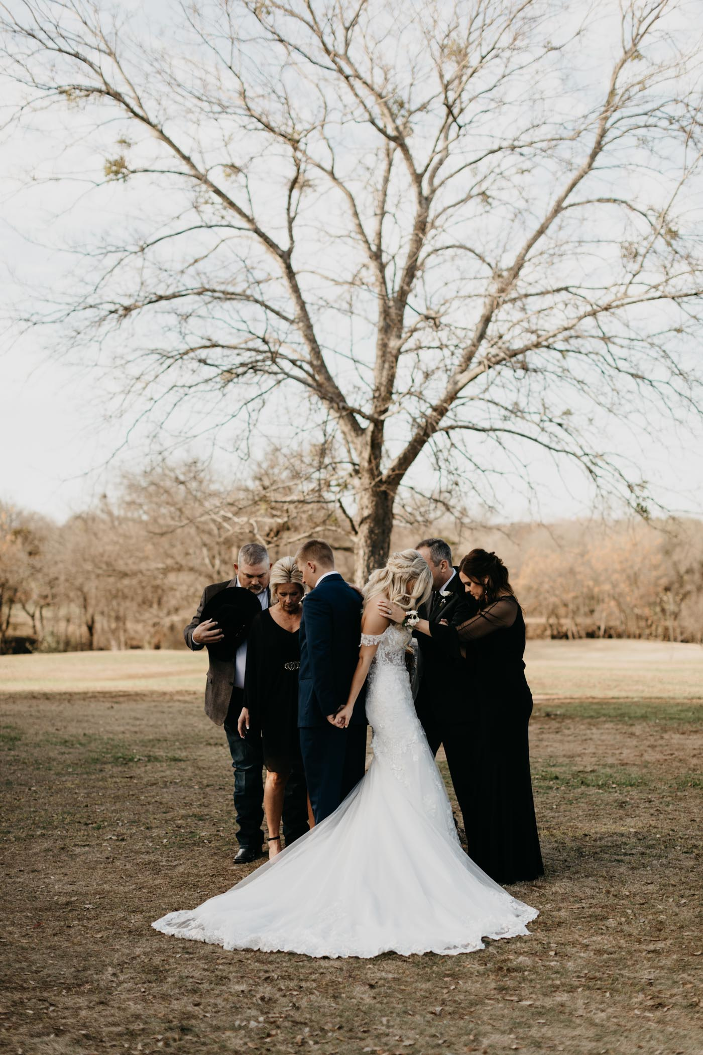 Bride and groom being prayed over before wedding ceremony starts