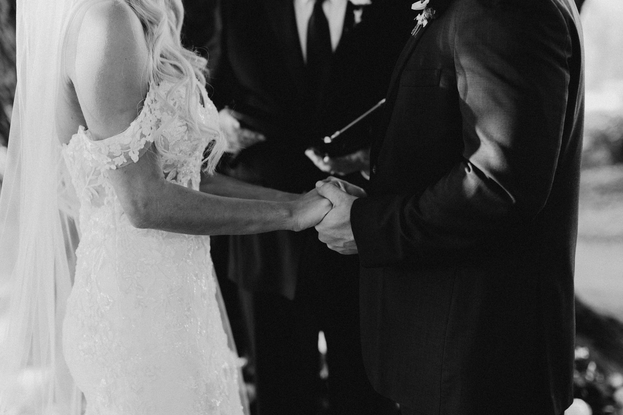 bride and groom holding hands after exchanging rings at ceremony