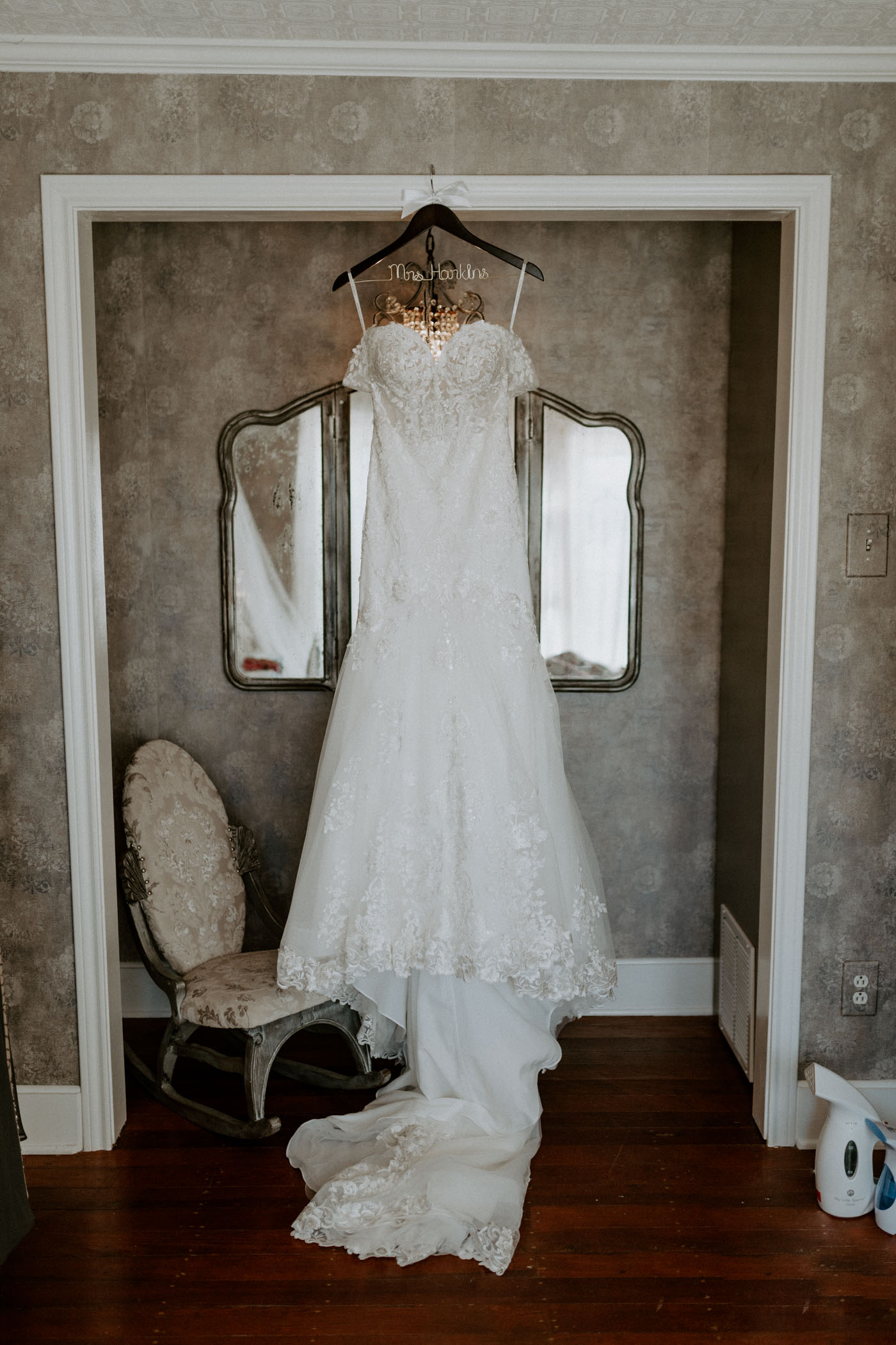 Lace wedding dress hanging in doorway of wedding venue