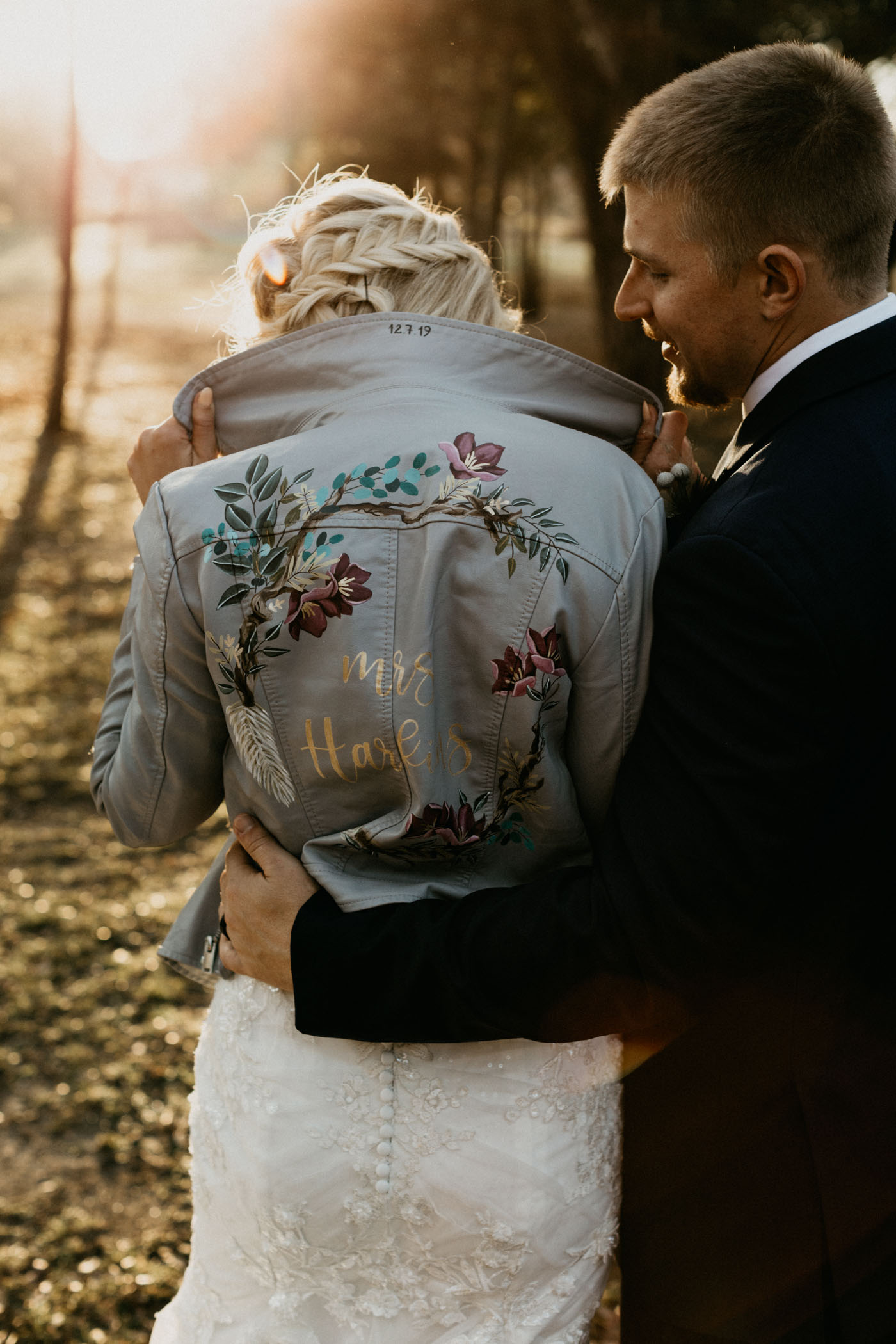 groom hugging bride as she is wearing a blue custom leather jacket
