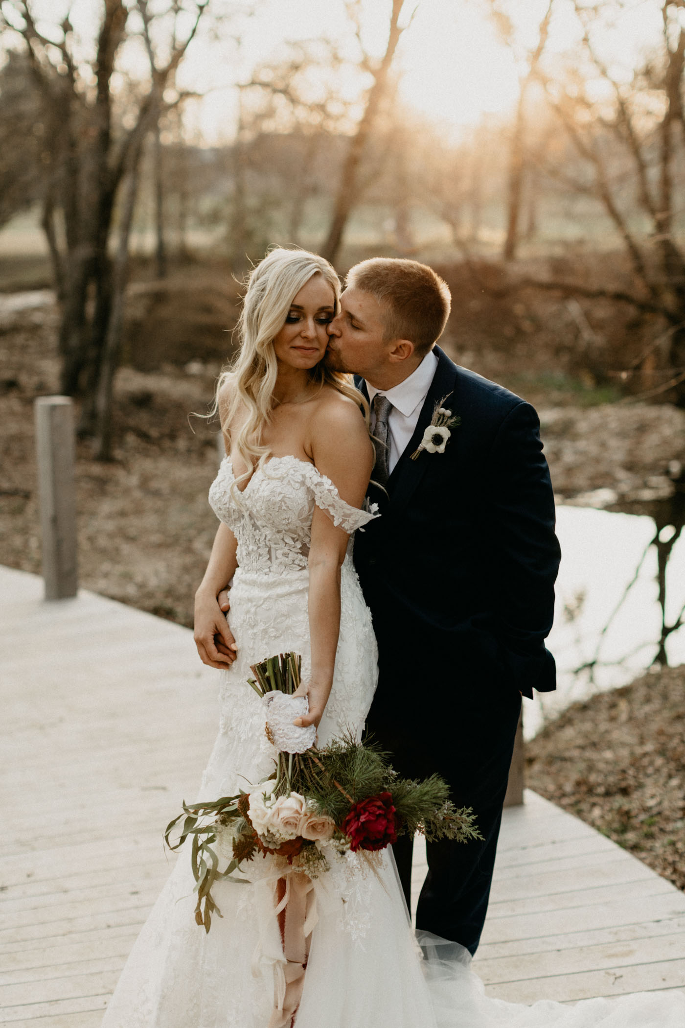 groom kissing girl on the cheek after wedding ceremony at golden hour in winter