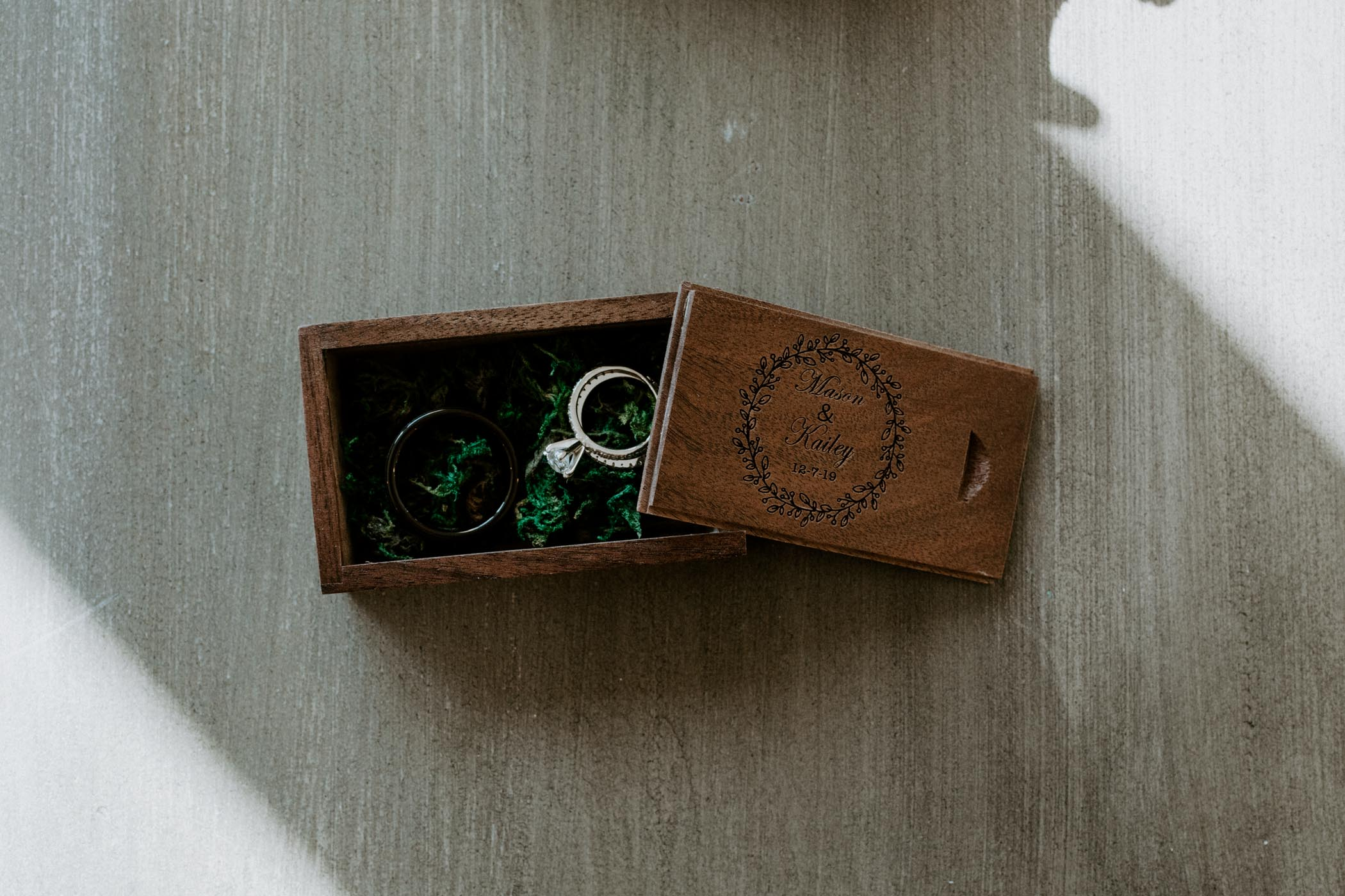 Wooden ring box detail photo on woodsy winter wedding day
