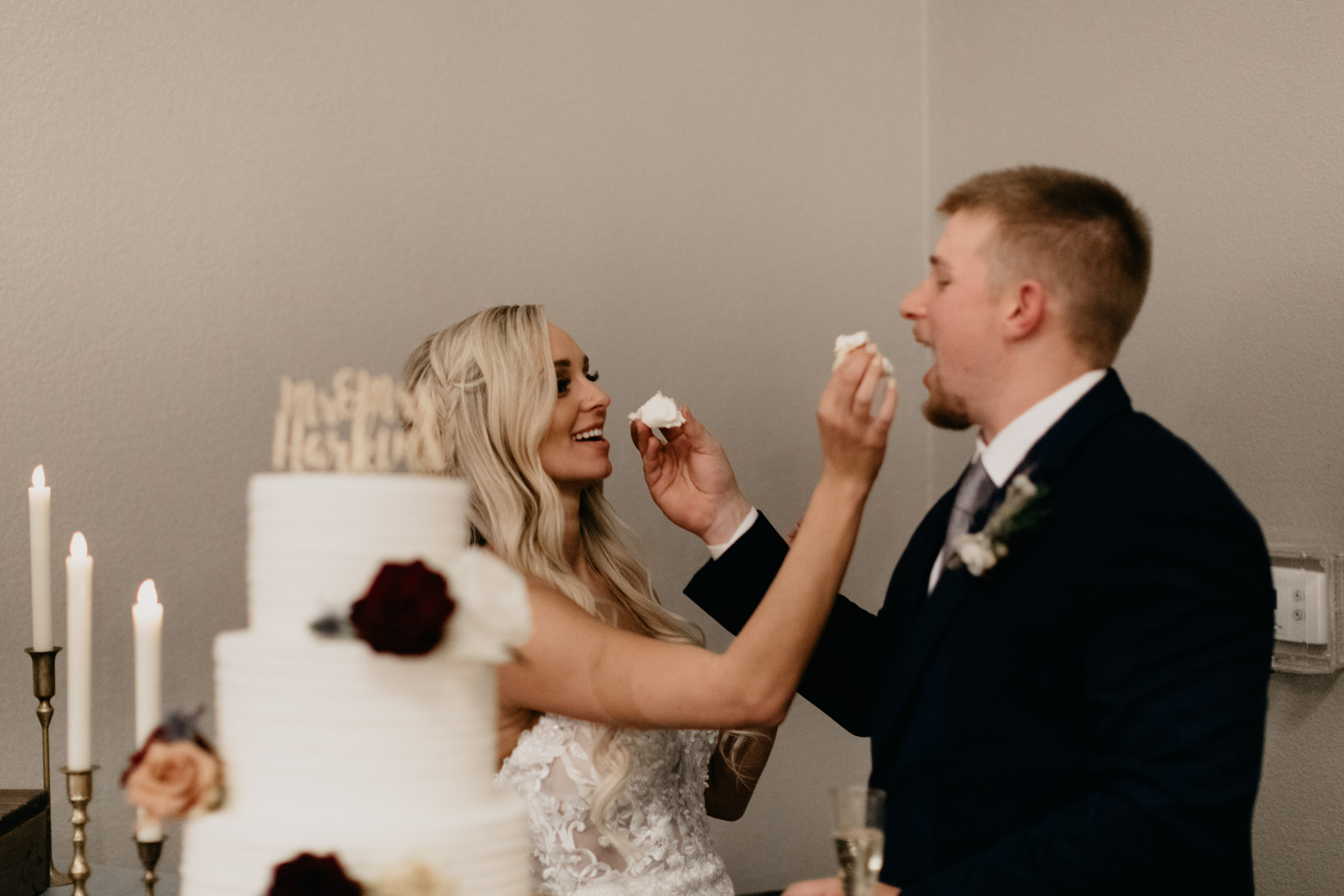 bride and groom feeding each other wedding cake