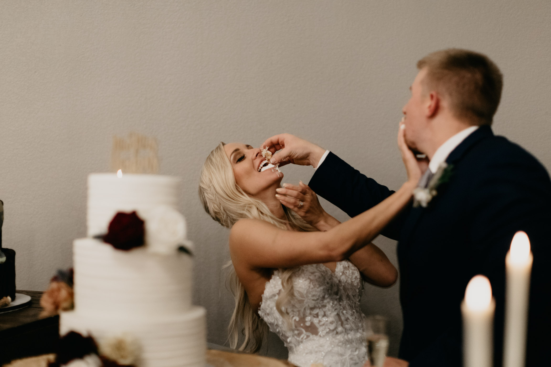 bride and groom shoving cake in each others faces during reception
