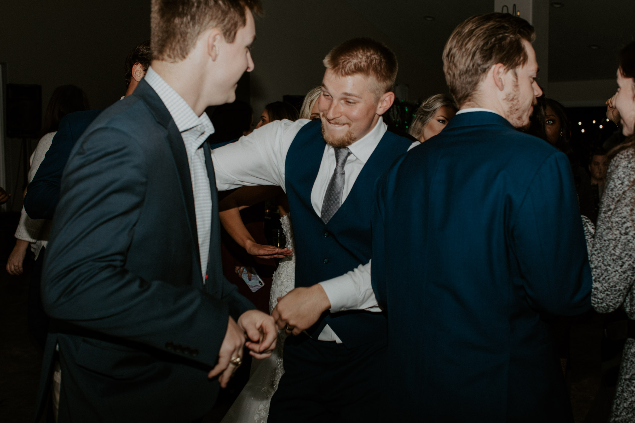 Groom dancing with groomsmen on wedding day