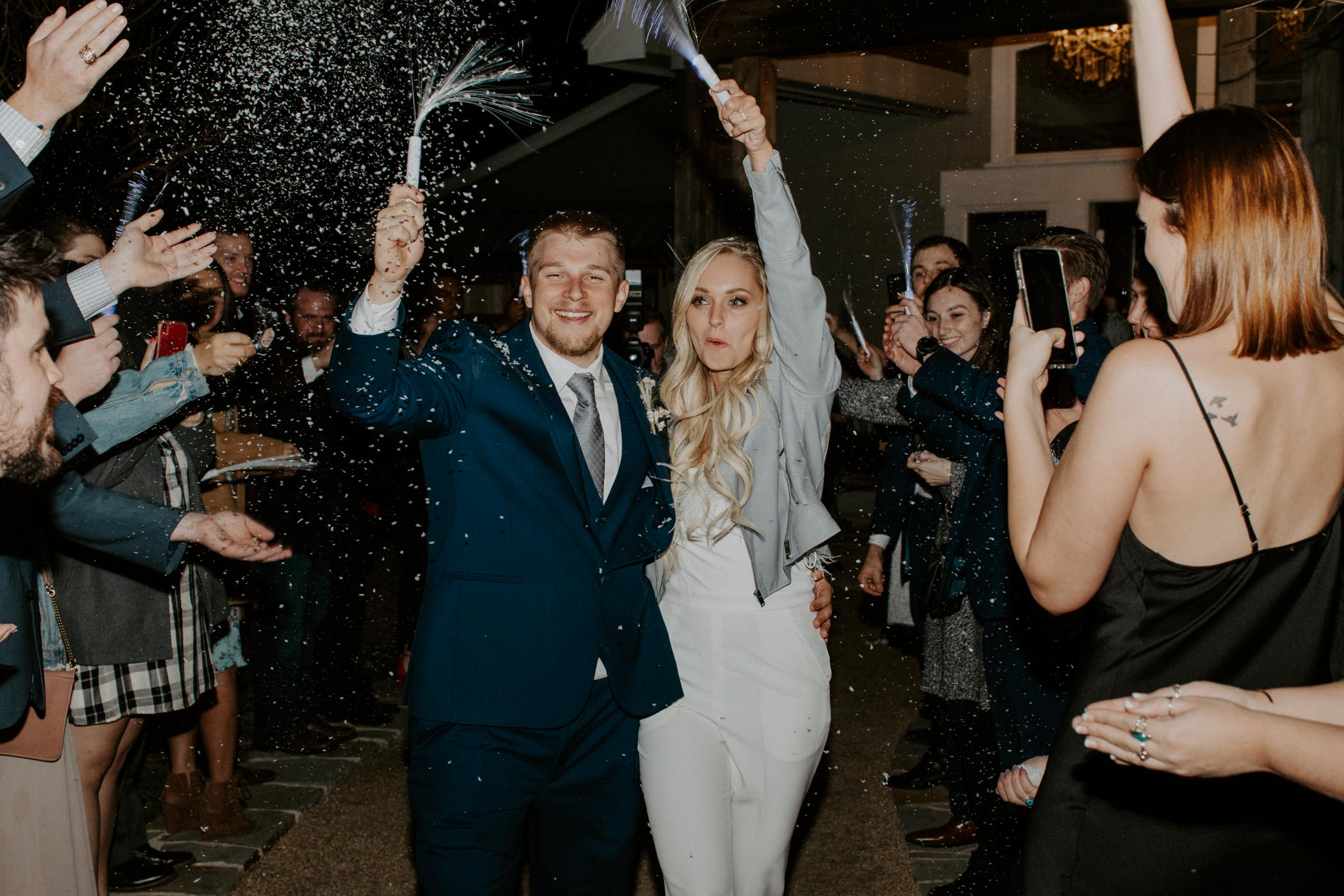 fun bride and groom running through guests during snow exit