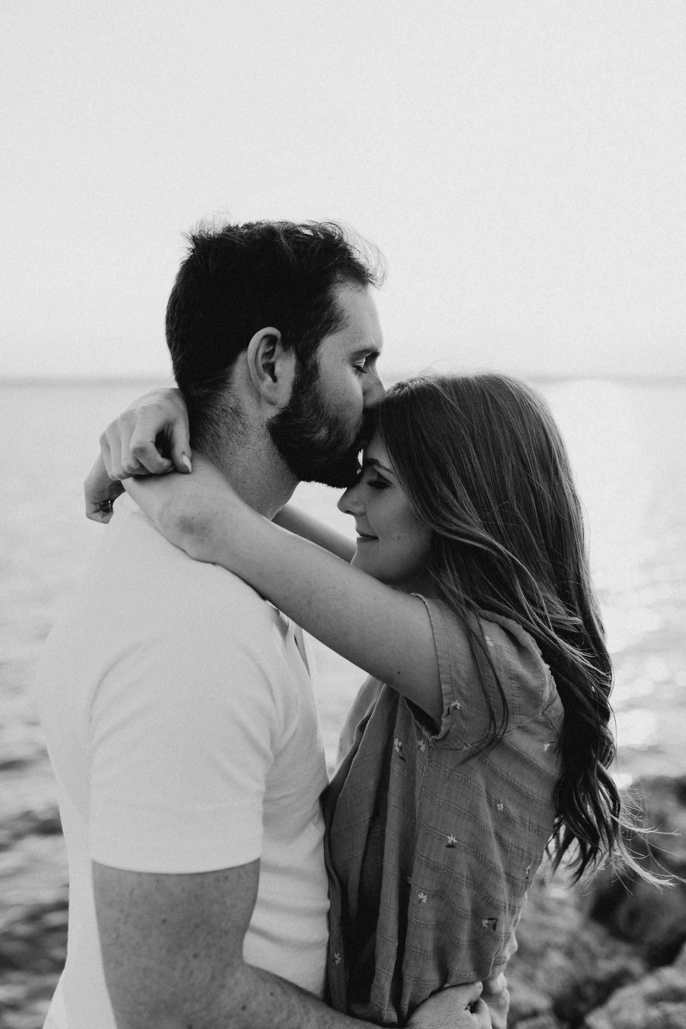 Moody black and white photo of engaged couple being romantic