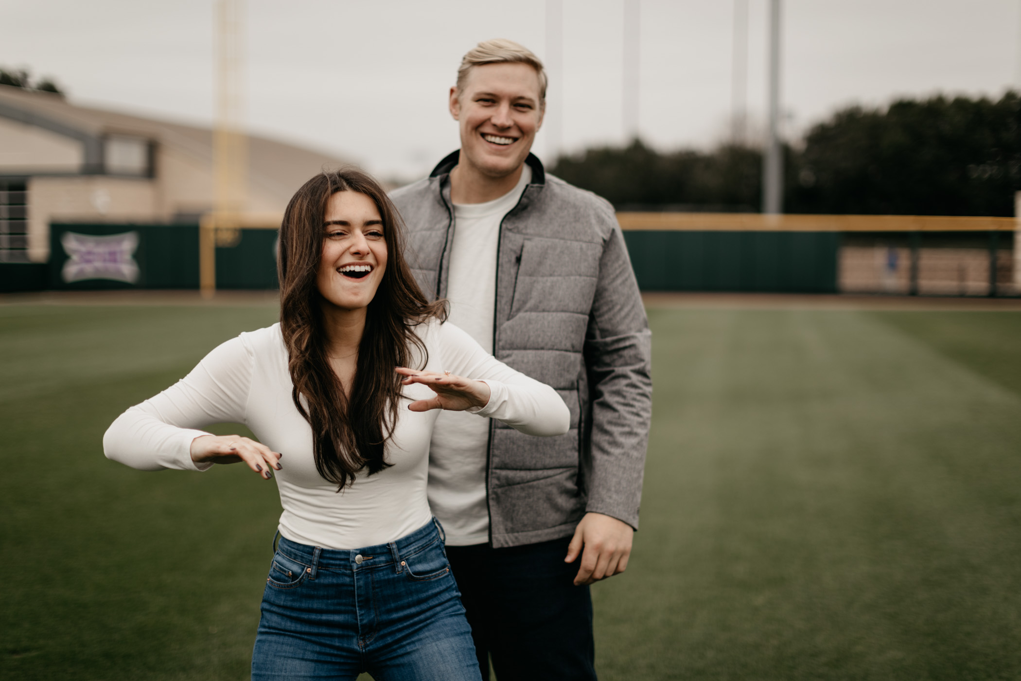 Playful photo of couple standing on TCU baseball field