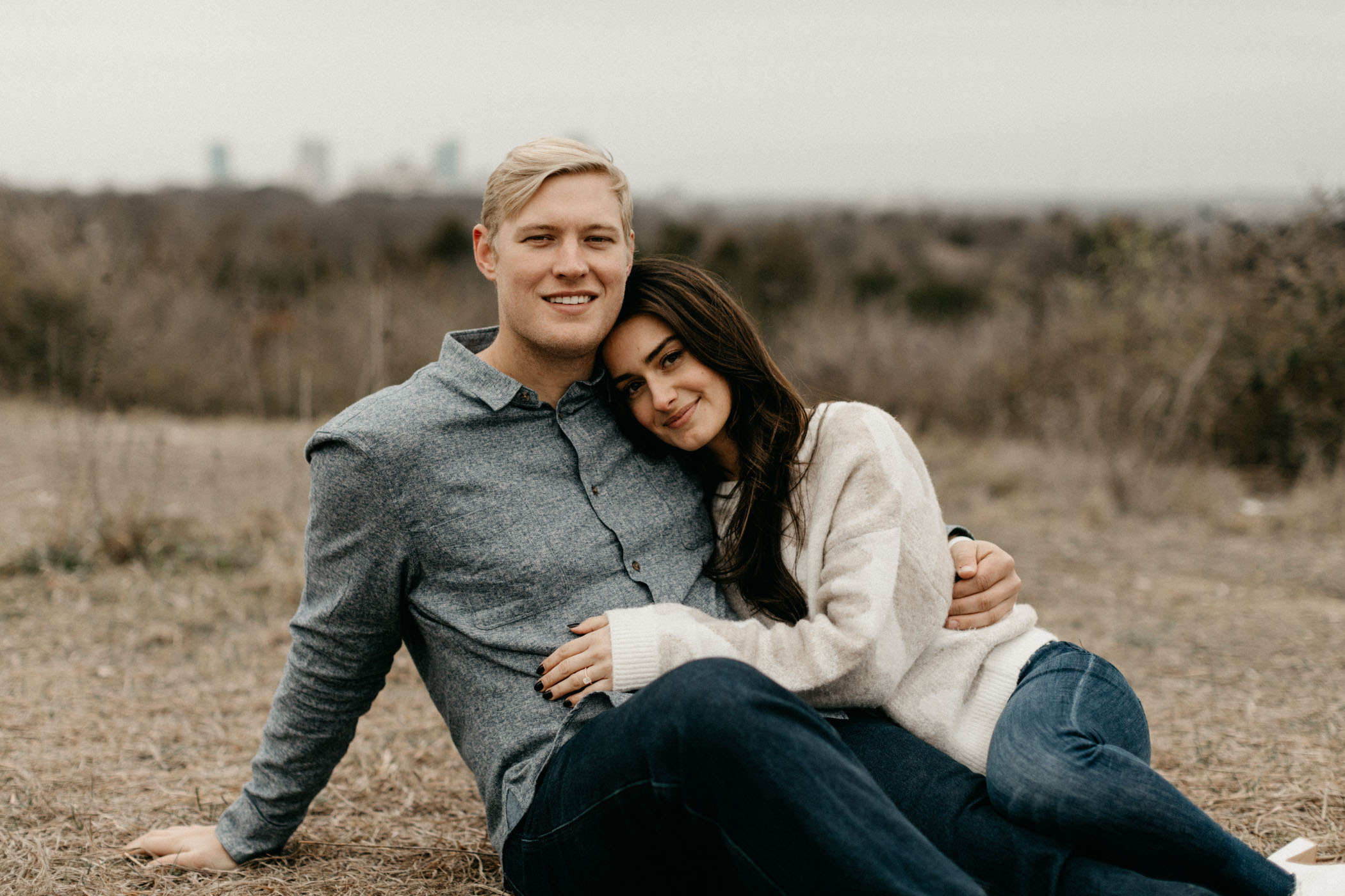 couple sitting in the grass and smiling during engagement session