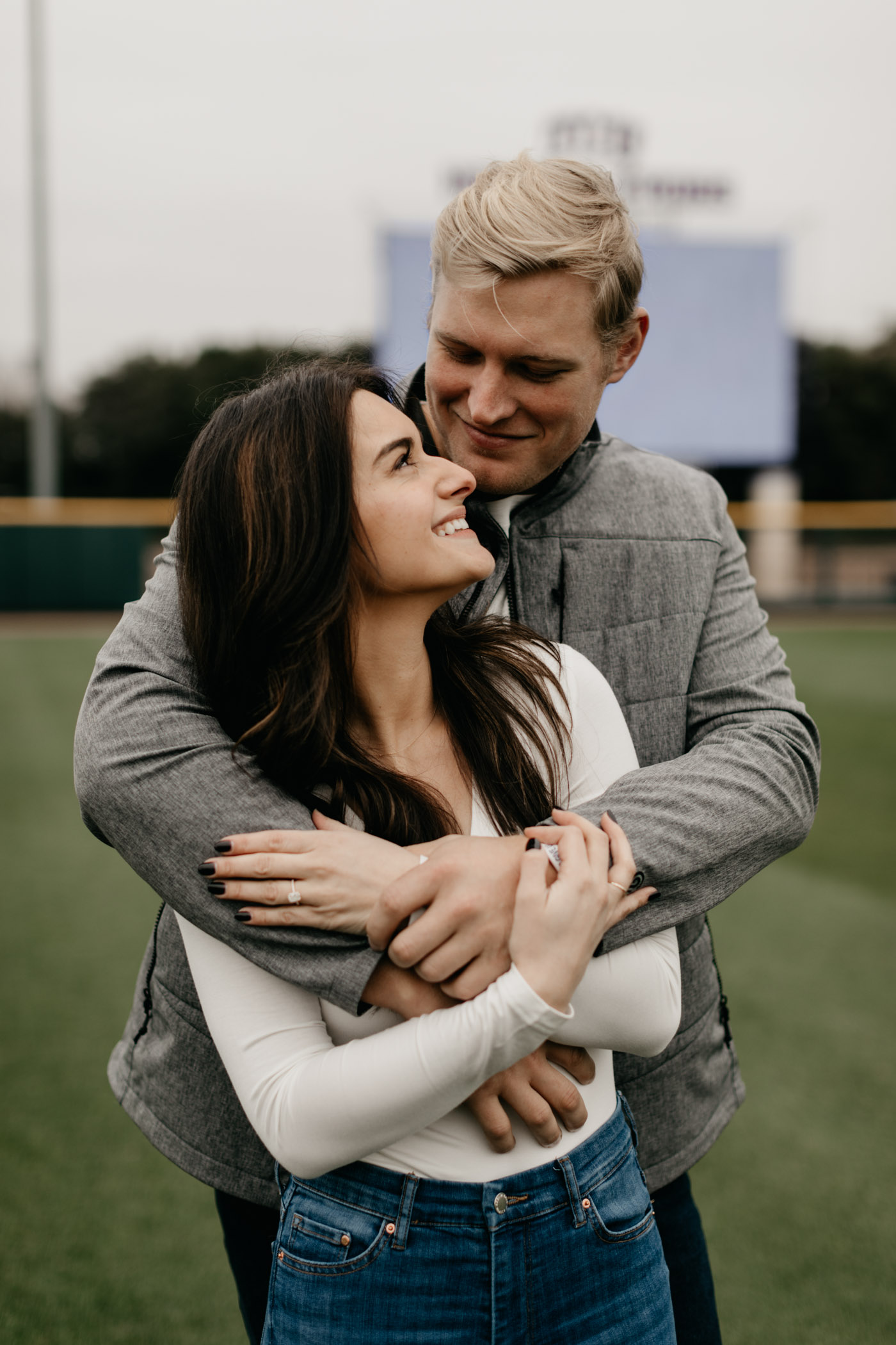 Luken baker hugging fiance at TCU baseball stadium for engagement photos