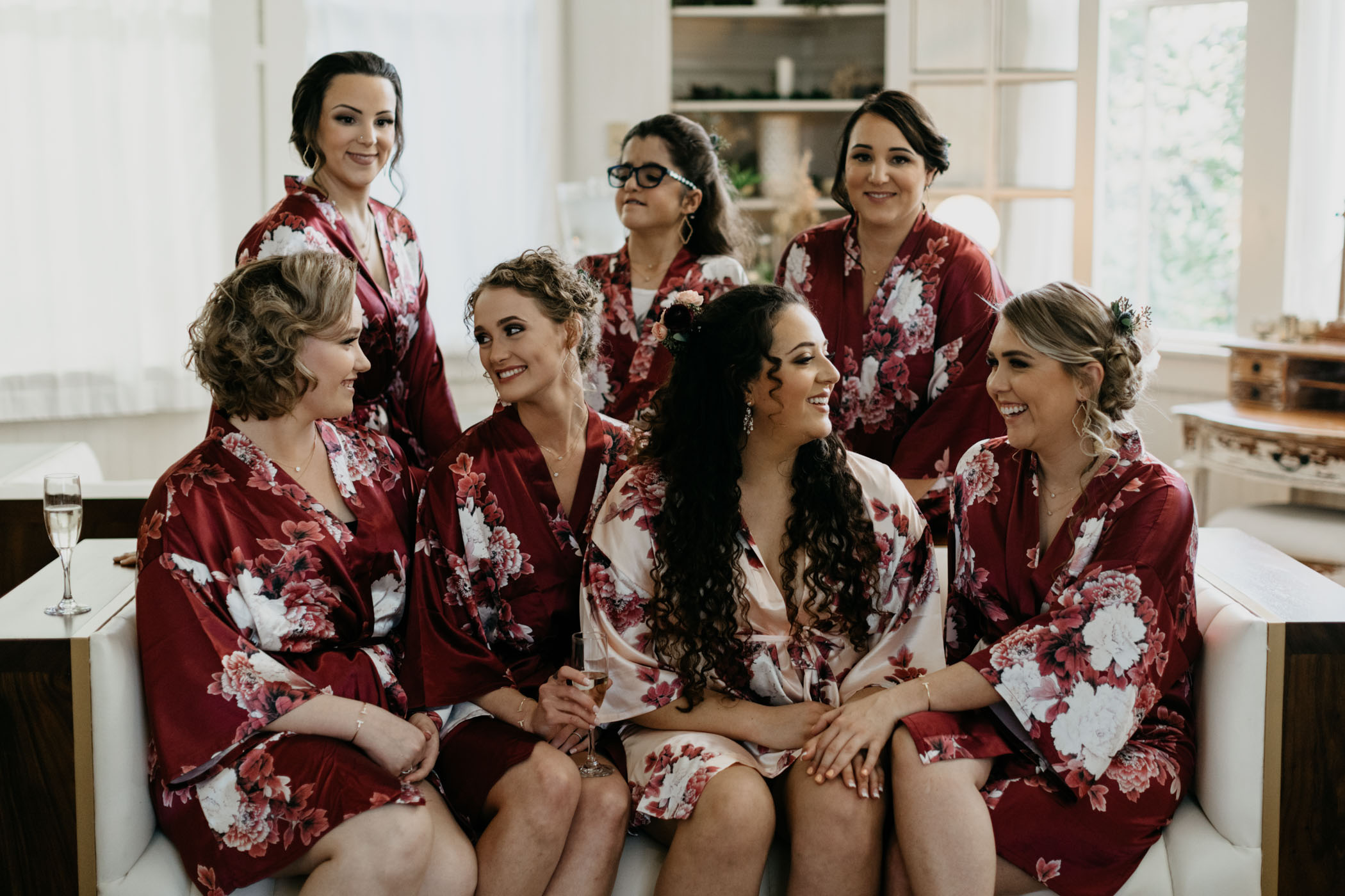 Bride and bridal party getting ready in maroon bridal robes on California wedding day