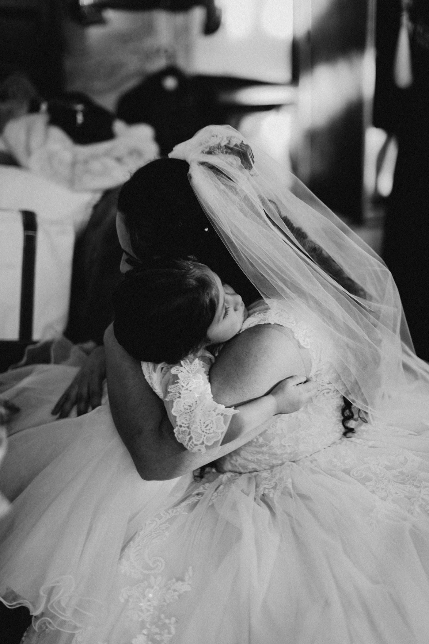 Moody black and white photo of bride hugging her flower girl