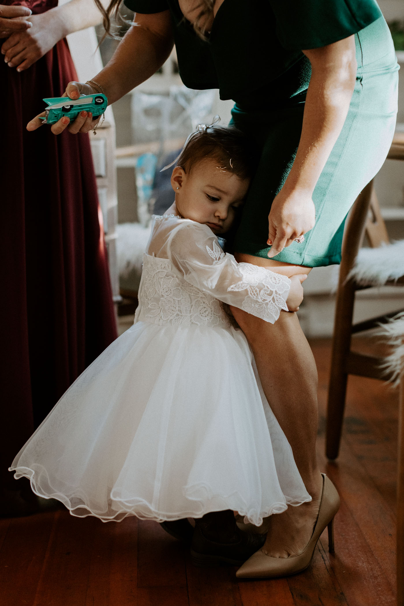 Flower girl hugging her mom before wedding ceremony starts