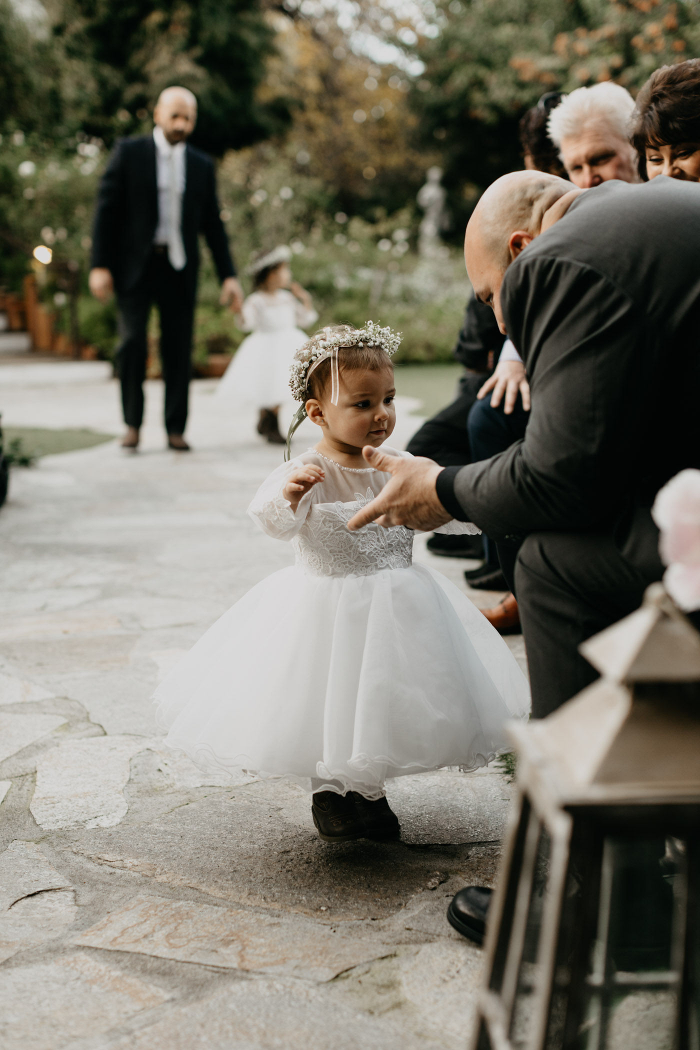 Young flower girl getting distracted as she walks down the aisle on wedding day