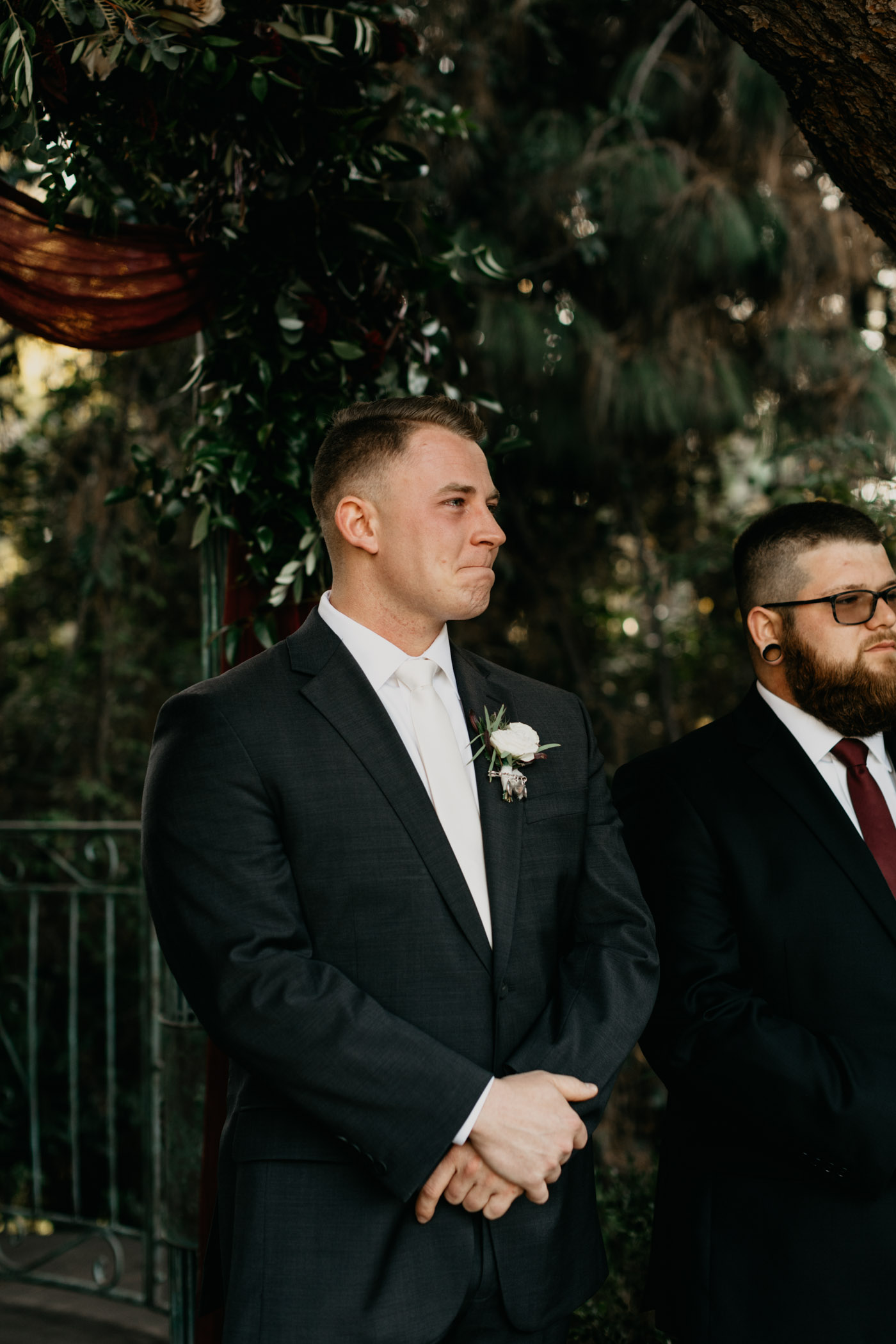 Groom holding back tears during his California wedding ceremony