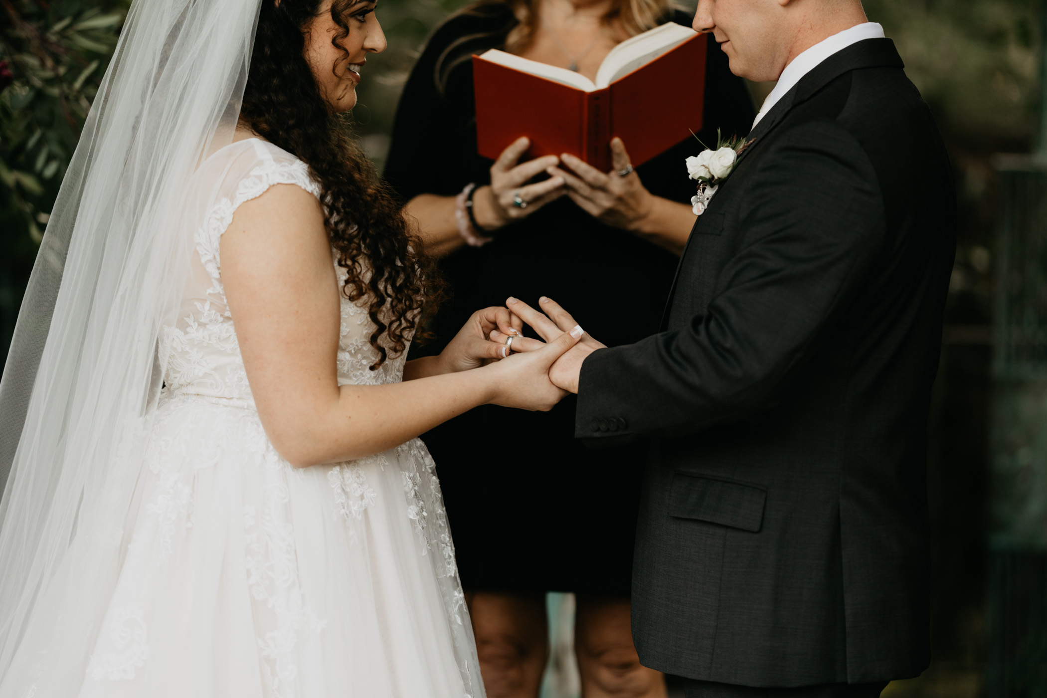 Bride and groom exchanging rings at their wedding ceremony in California
