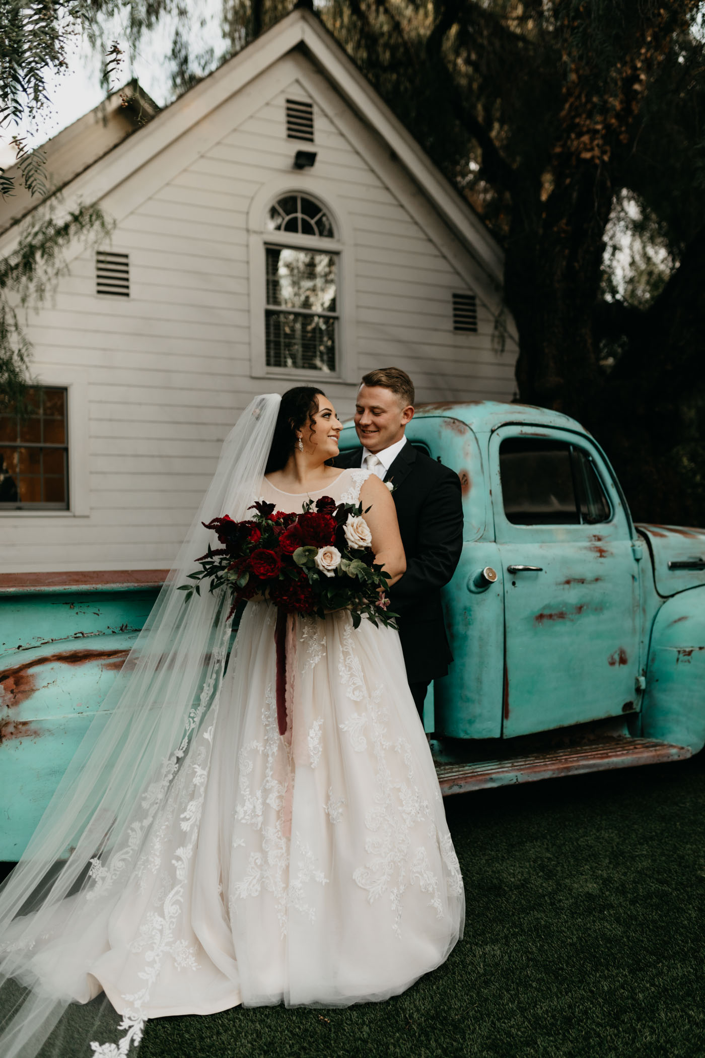Bride and groom pose in front of vintage pickup at wedding venue