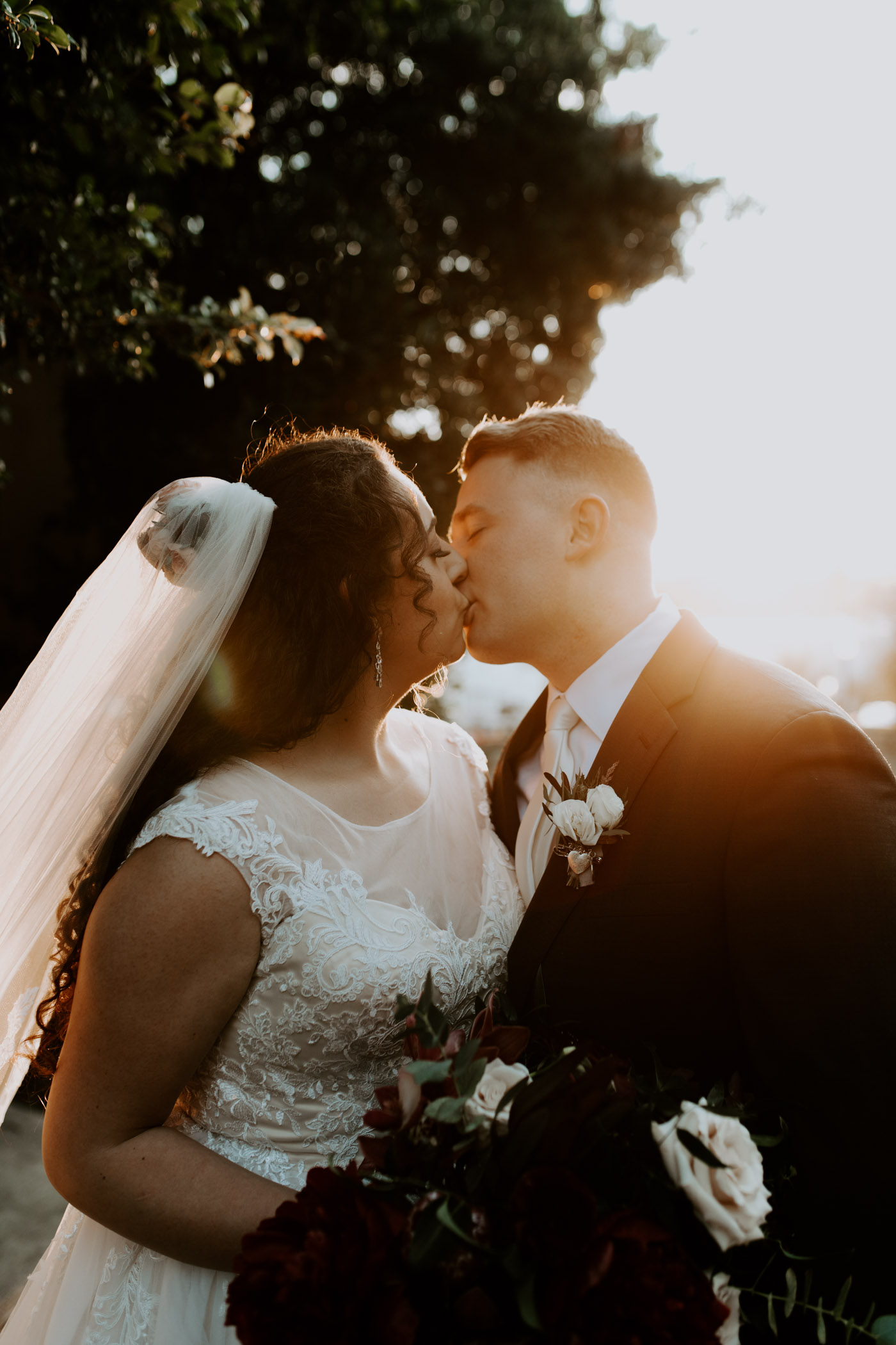 Bride and groom kissing at golden hour at their wedding venue