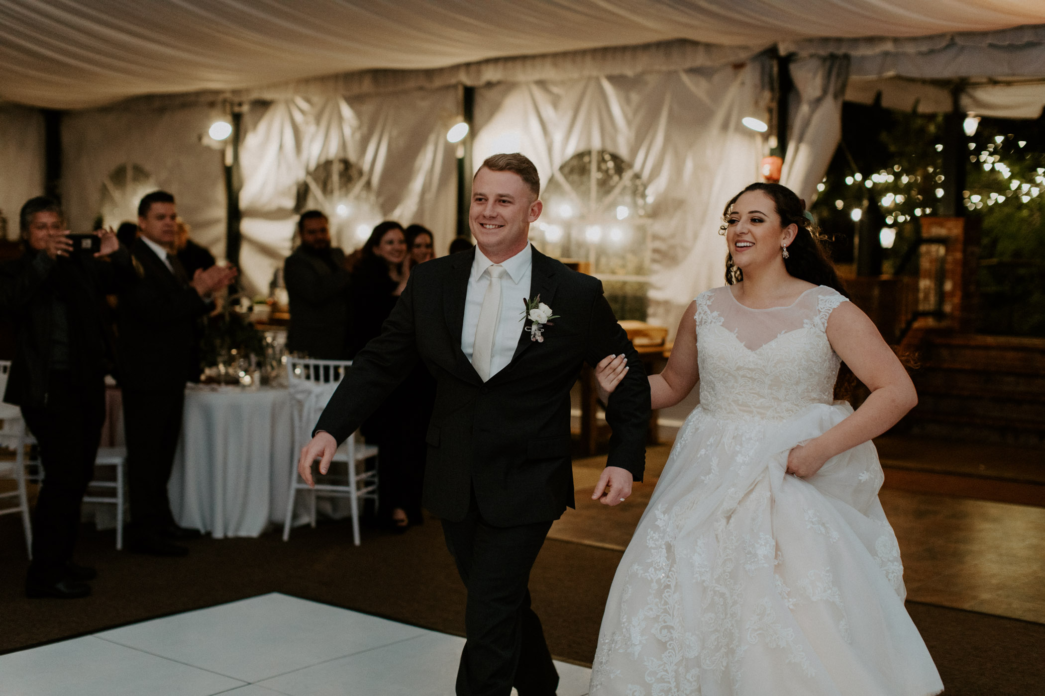 Bride and groom entering their wedding reception at green gables estates in San Marcos California