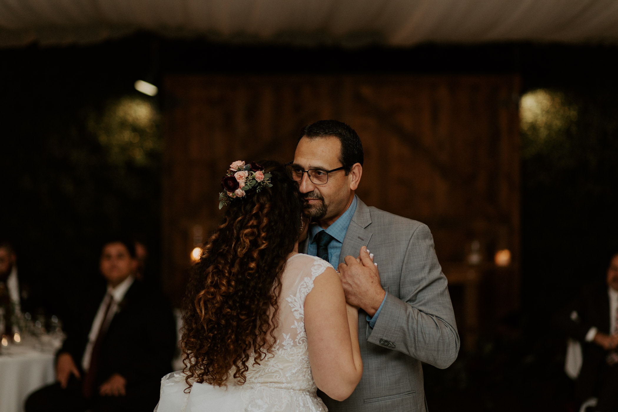Dad holding daughter close as they share a dance on her wedding day