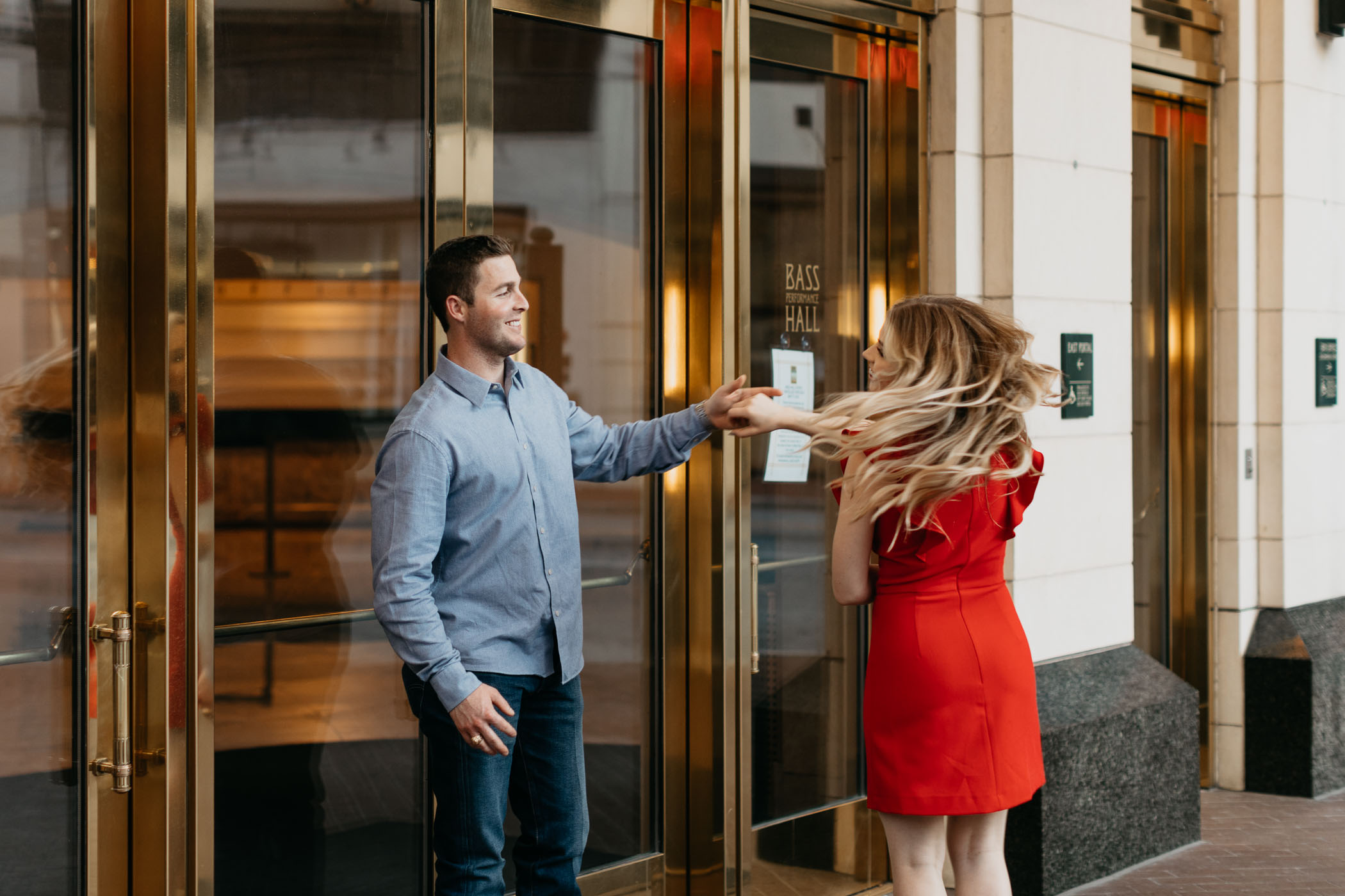 Couple dancing in front of Bass Hall during downtown Fort Worth engagement session