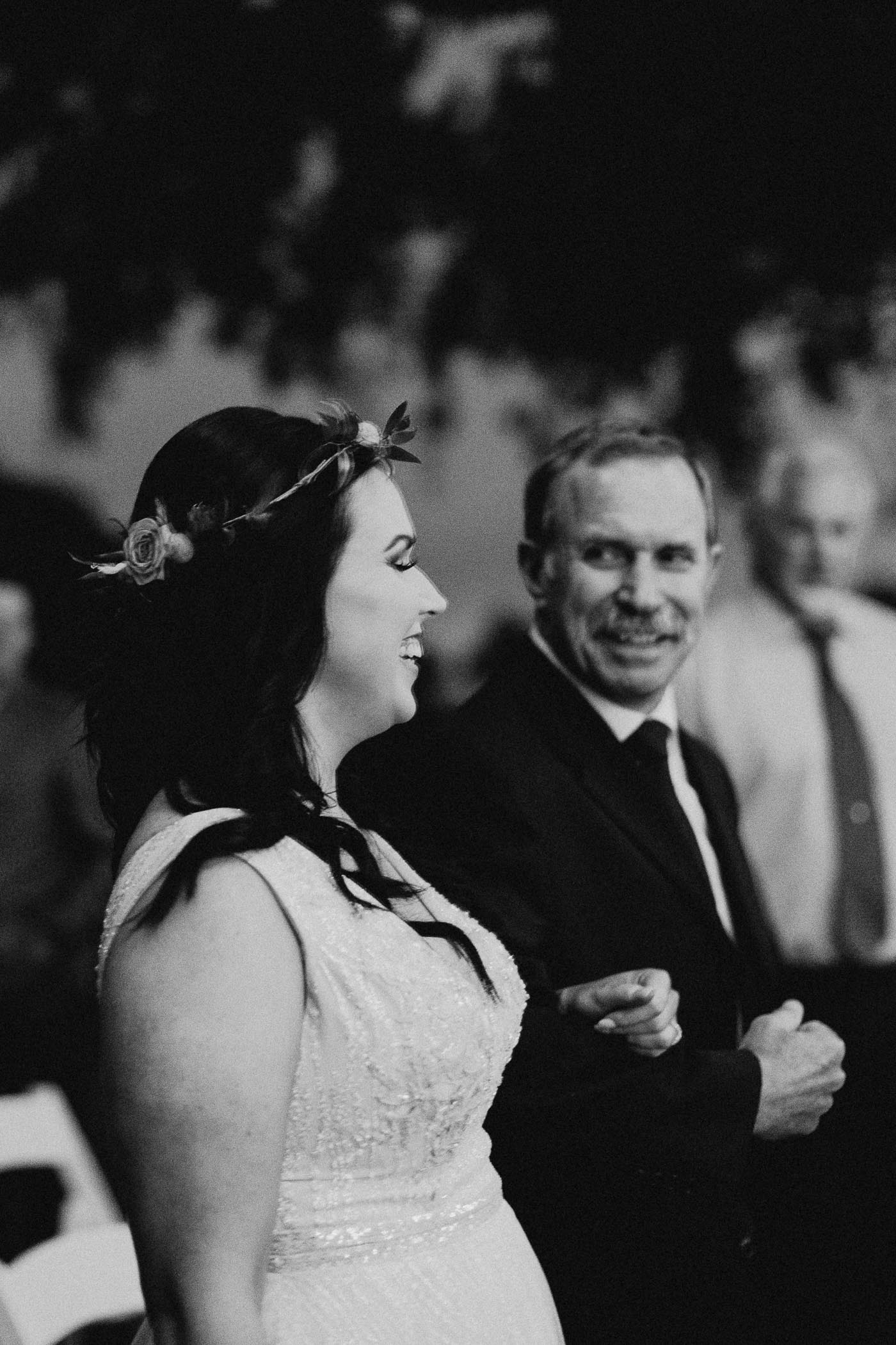 Black and white photo of dad walking bride down the aisle on her wedding day