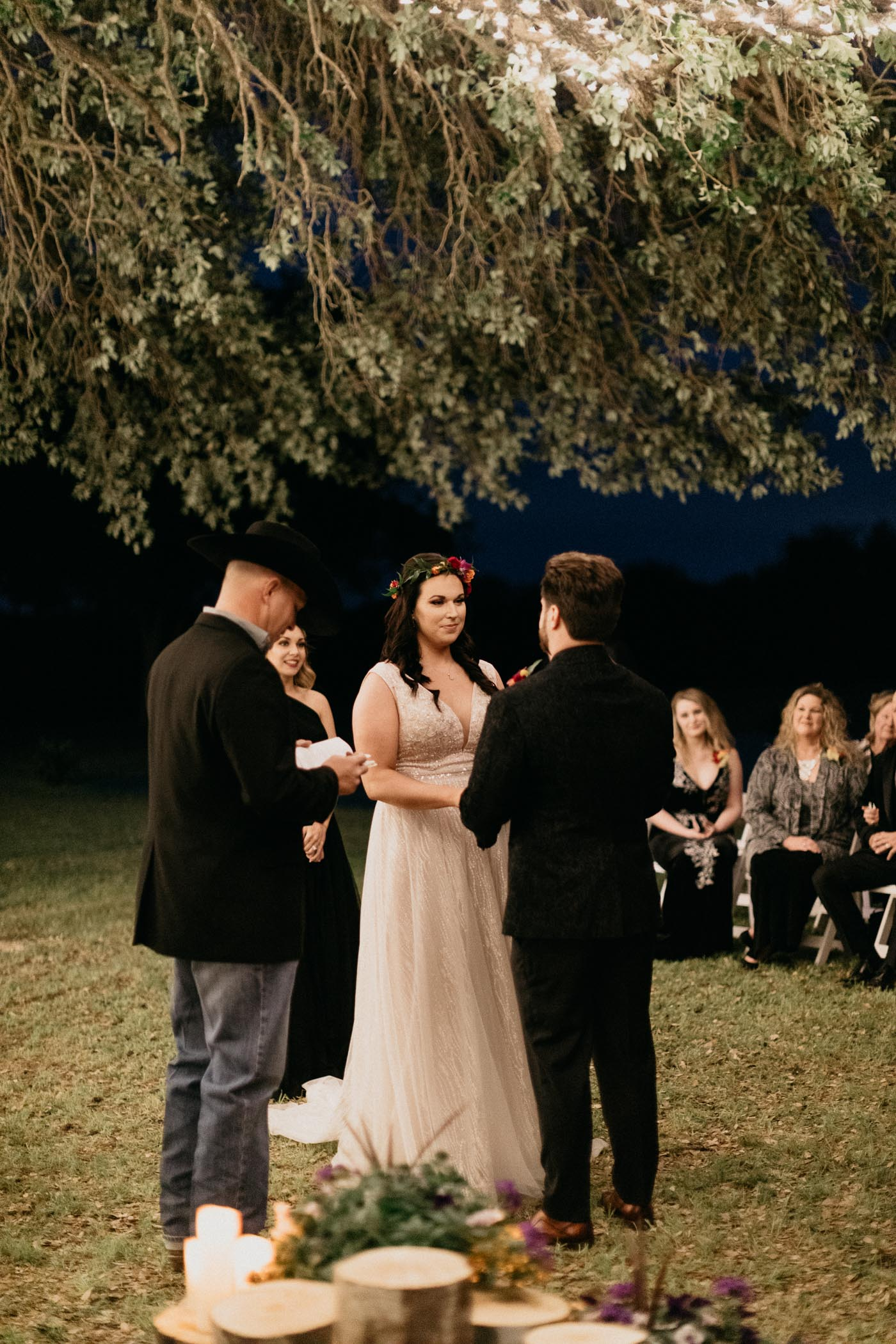 Bride and groom looking at each other during outdoor wedding ceremony at night time