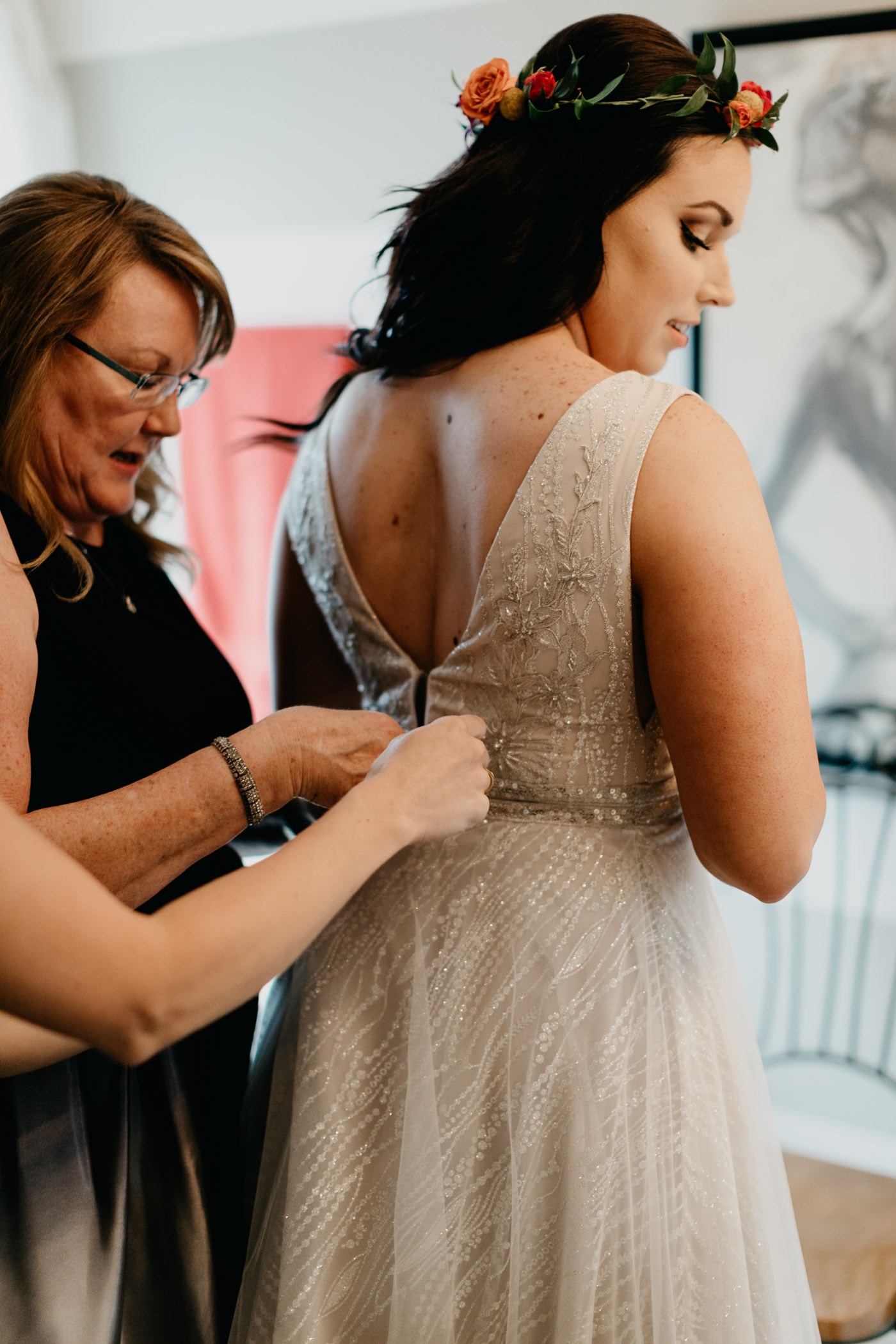 Brides mom zipping her dress on her wedding day