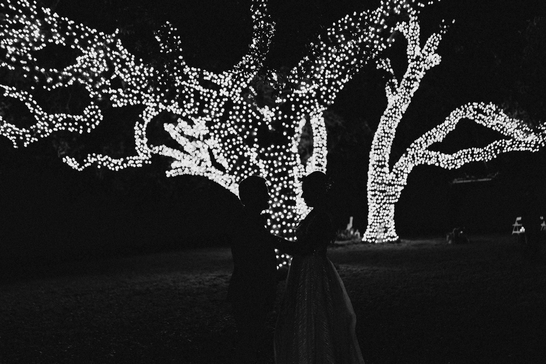 Black and white silhouette of bride and groom in front of string lights