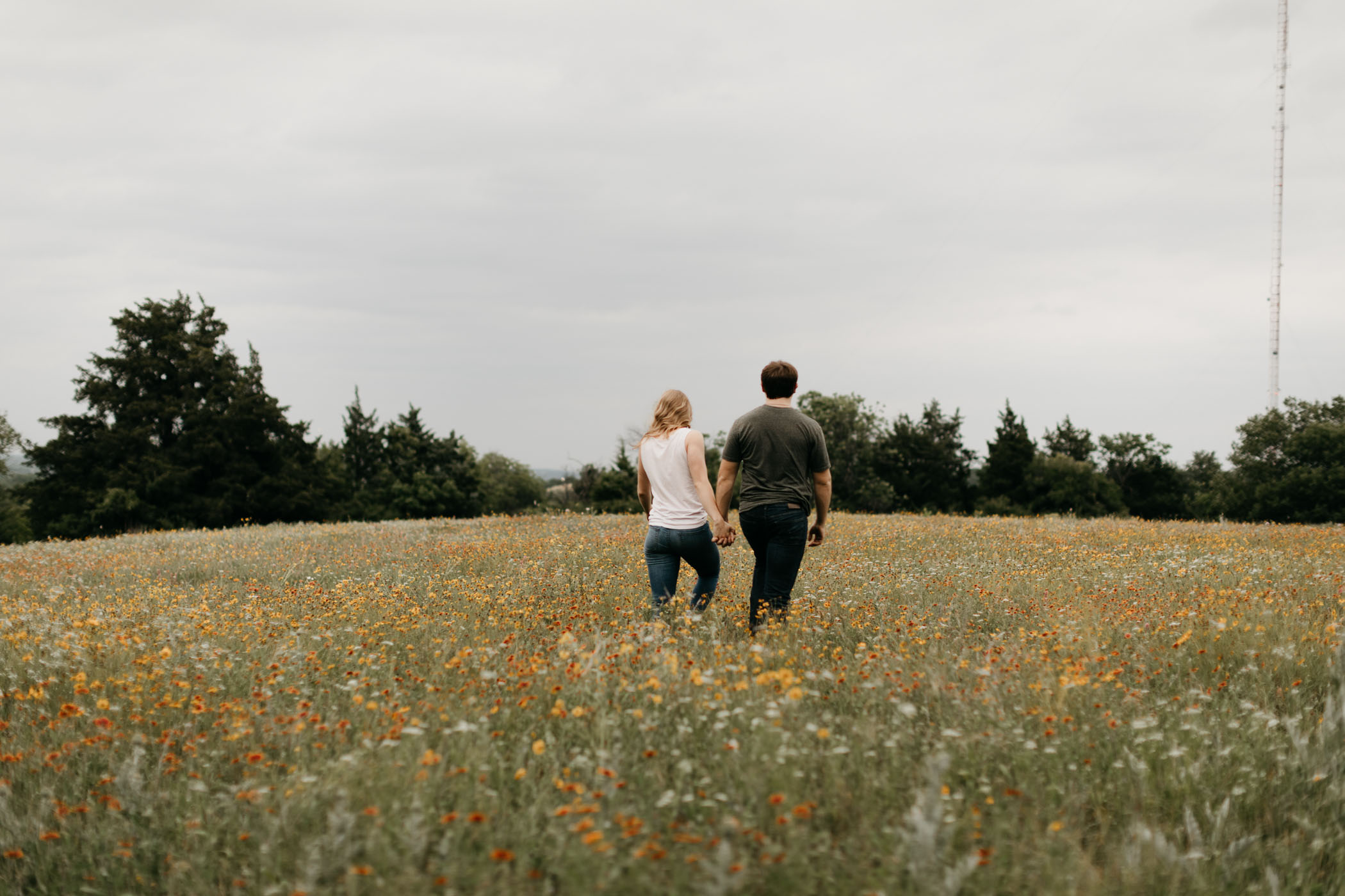 couple walking through field of wildflowers during engagement session