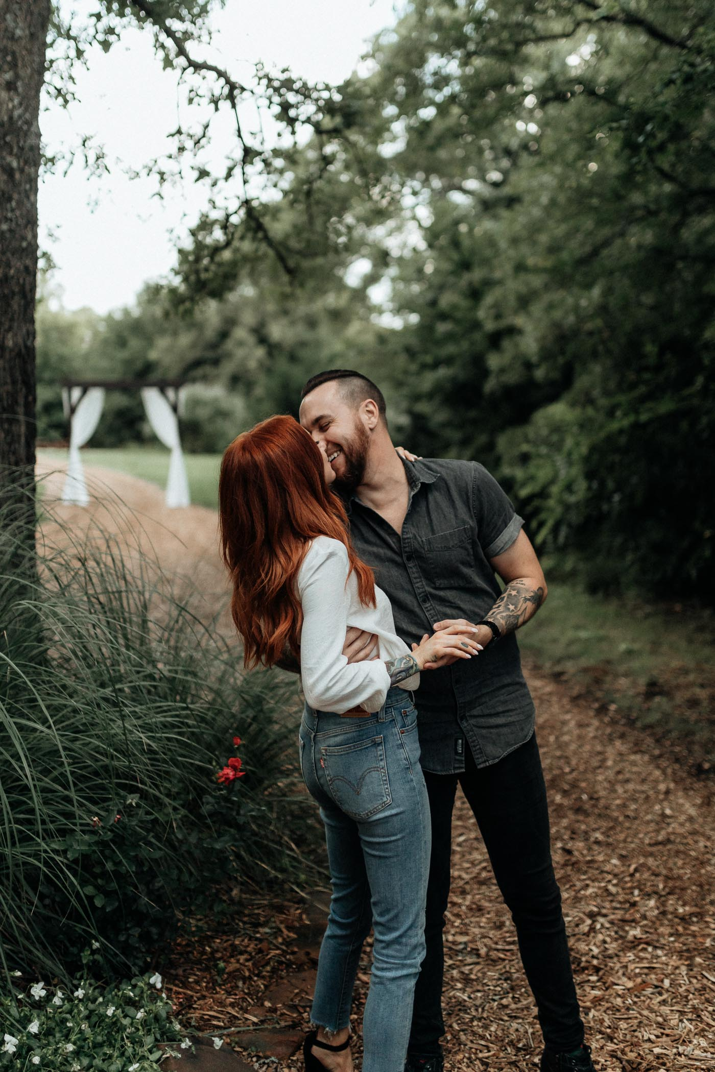 Couple standing in woodsy area of the grove in Auburn Texas