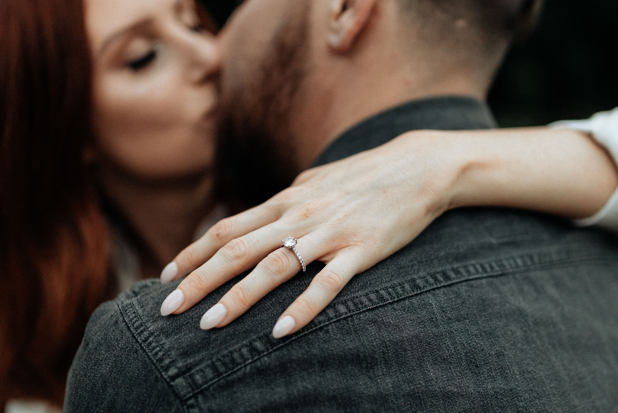 Detail photo of engaged girl wearing wedding ring and kissing her fiancé in DFW