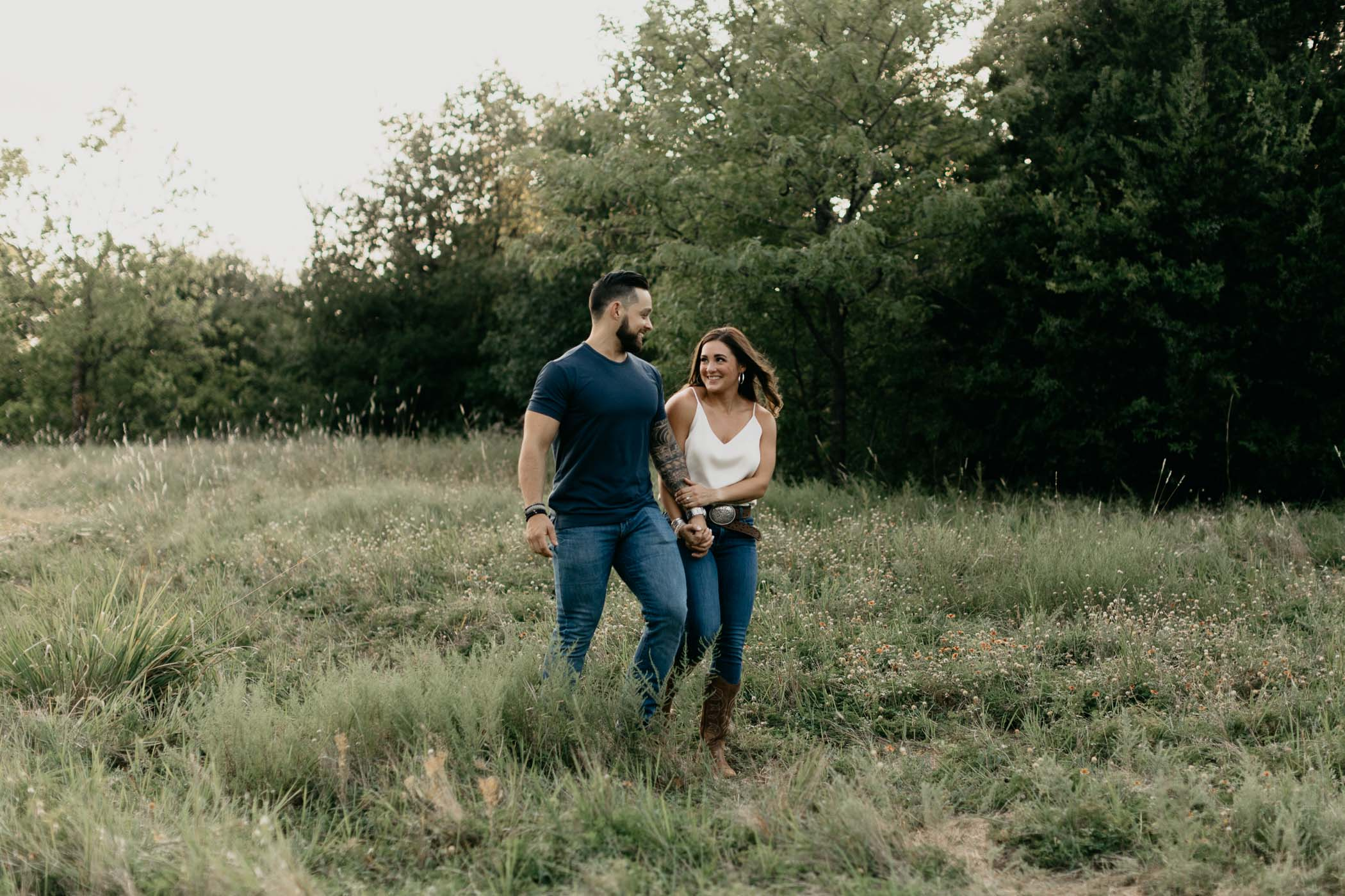 Engaged couple walking through field in DFW during photo session